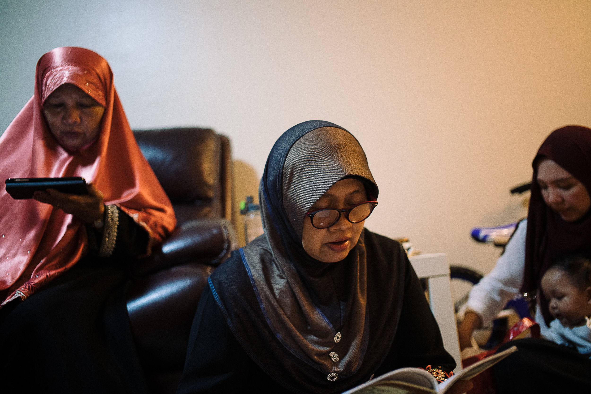 Hidayah's mother (L), mother-in-law (M), and sister-in-law (R) reciting the Yaseen, or the heart of the Qur'an, and praying it for Hana's well-being.