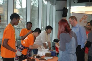 Young people from ReachOut taking part in social action, selling cakes for charity.