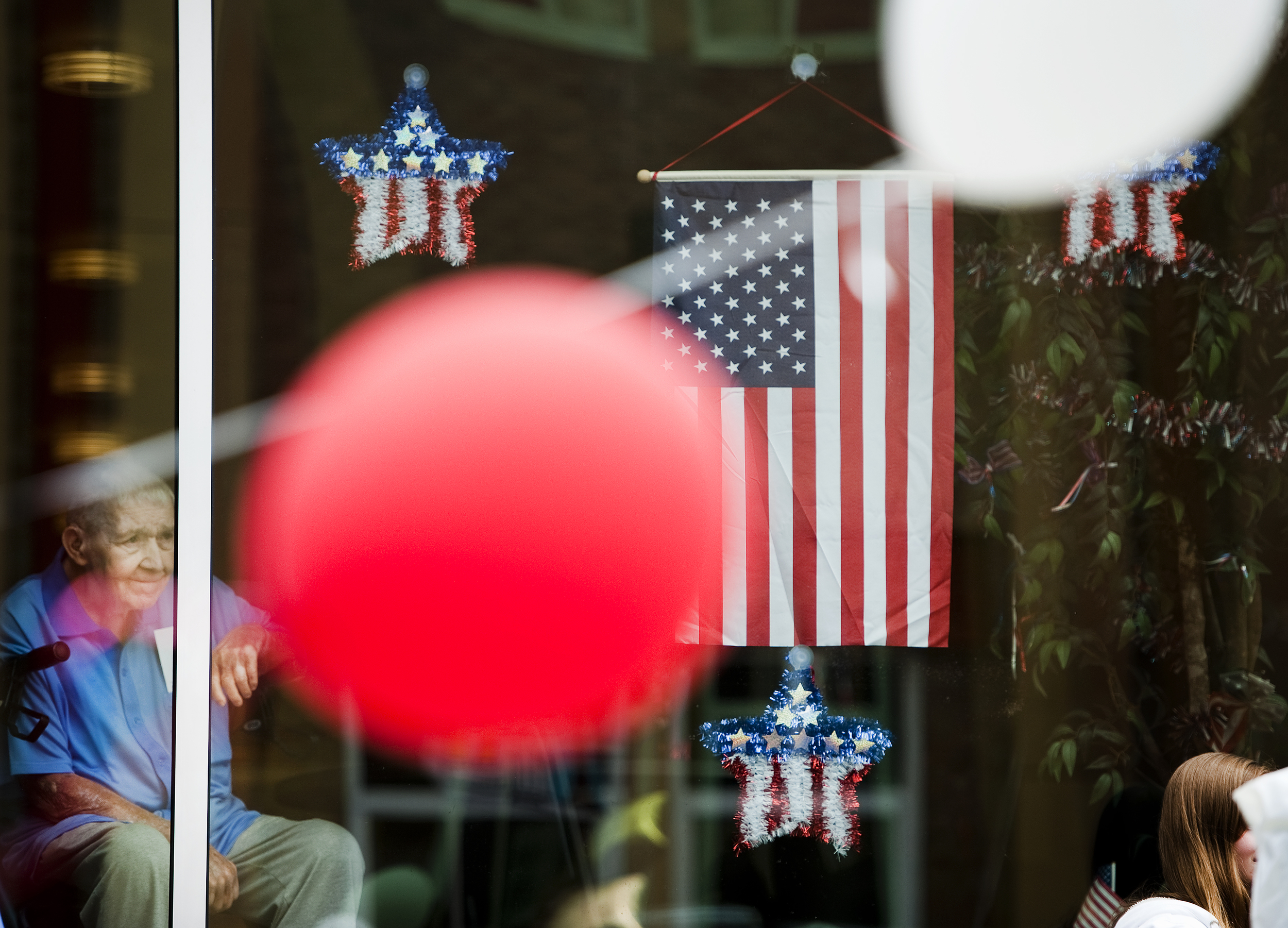 """Army veteran Darrell Moody, 88, of Latrobe watches floats from inside his assisted living home during the 4th of July Parade on Saturday, July 4, 2015 in Latrobe. """"I am a World War II veteran, a Korean veteran and a veteran here (in the home),"""" Moody said laughing."""