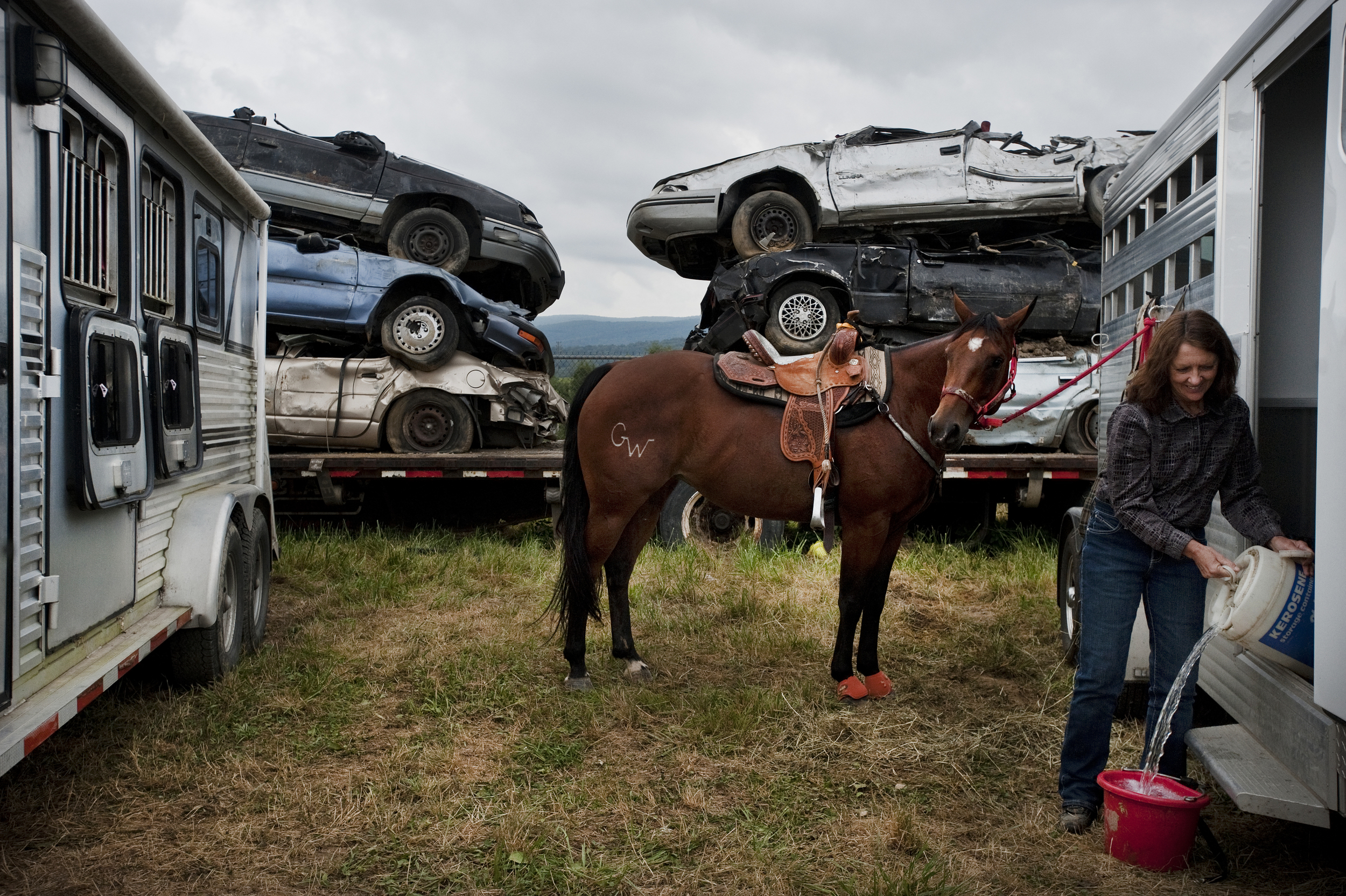 Demolished cars make for an unusual backdrop for 6-year-old horse Macy as owner Doreen Ulery of Bullskin cares for her before a rodeo at the Fayette County Fair on Thursday, Aug. 6, 2015 in Dunbar.