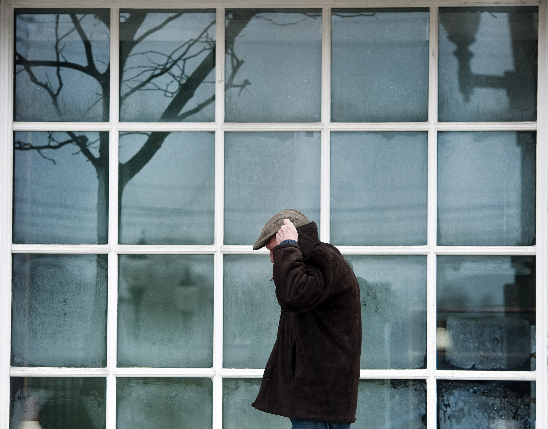 Steven Kaminski of Greensburg lifts his collar over his ears while smoking a cigar past a frosty window along Main Street in Greensburg on Monday, Jan 18., 2016. The National Weather Service has issued a wind chill advisory until noon Monday. Winds are expected at 10-15 mph, with gusts up to 25 mph.
