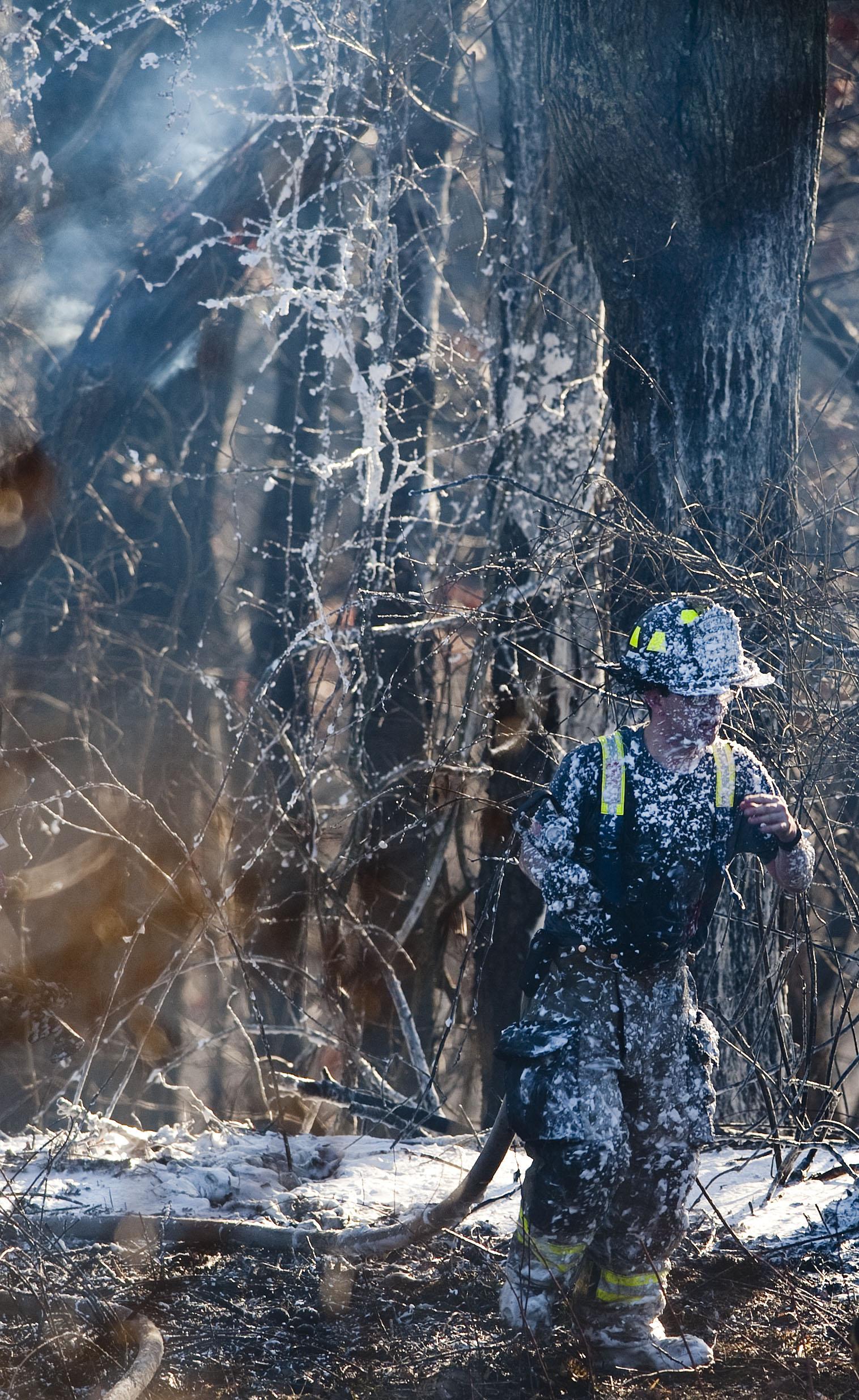 A firefighter knocks down a brush fire behind Hempfield Area High School on Saturday, Feb. 20, 2016.