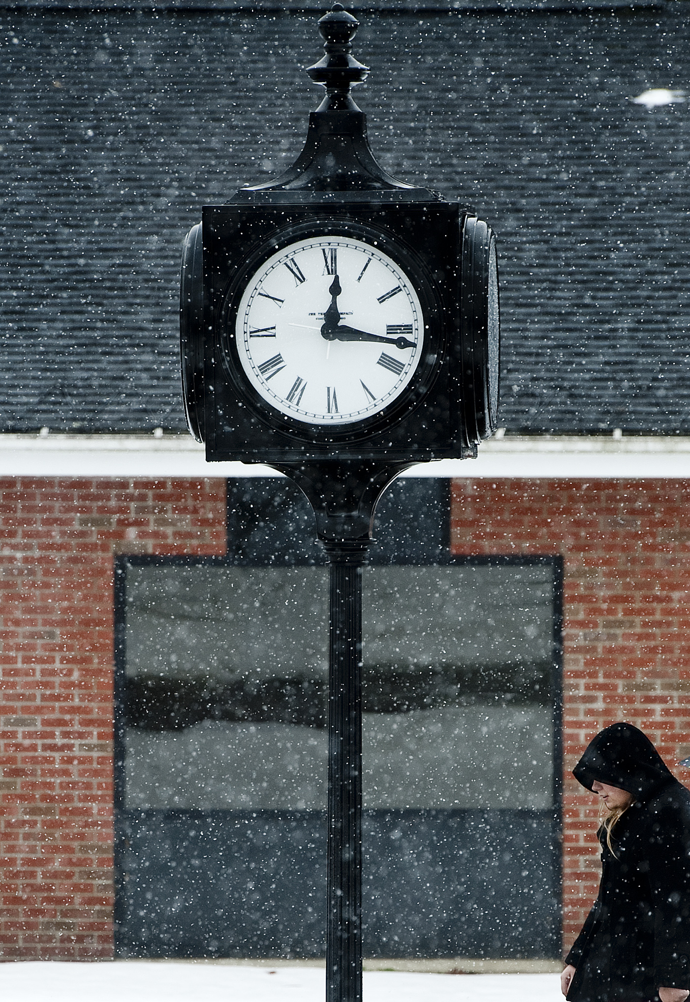 A wintery mix of freezing rain and snow surround a woman as she walks underneath a clock at the University of Pittsburgh at Greensburg on Tuesday, Feb. 16, 2016.