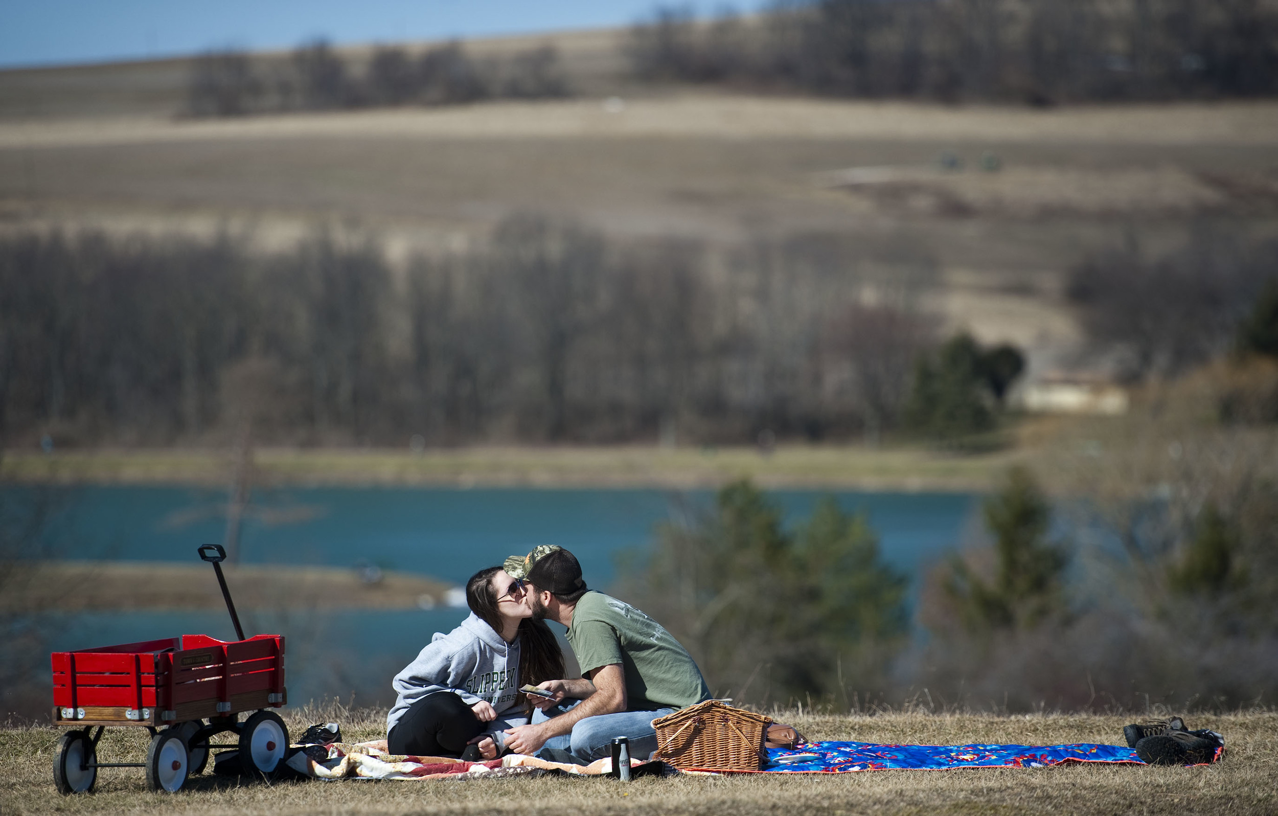 Abby Wirth kisses her boyfriend Shane Ostrosky after Ostrosky scratched off a lottery ticket worth $50 while the couple enjoys a picnic in the 60-degree weather on Saturday, Feb. 20, 2016 at Mammoth Park near Mt. Pleasant.