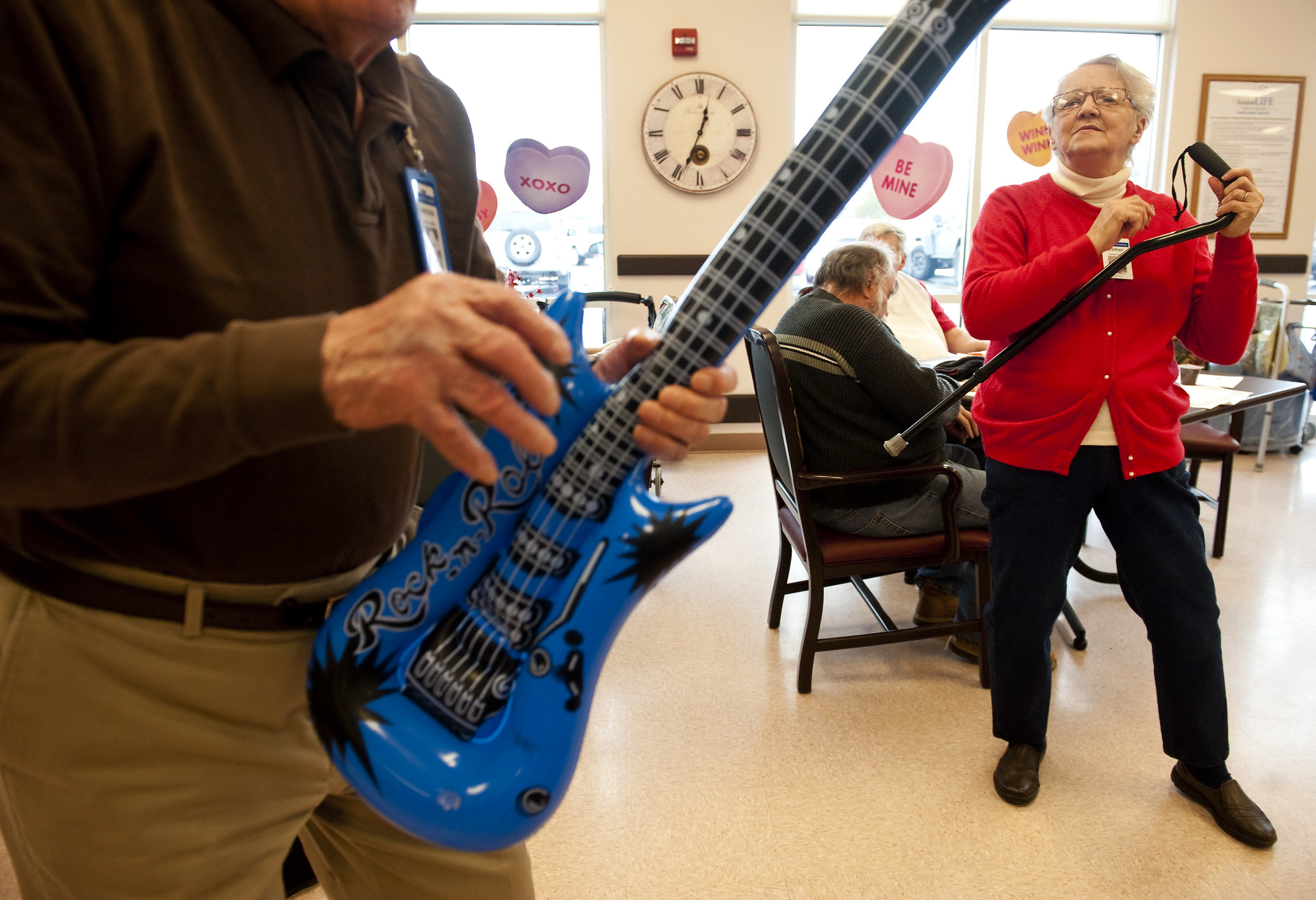 """Esther Czekaj, 75 of Mt. Pleasant, uses her cane as an """"air guitar"""" during a Valentine's dance at Senior LIFE in Greensburg on Monday, Feb. 15, 2016."""