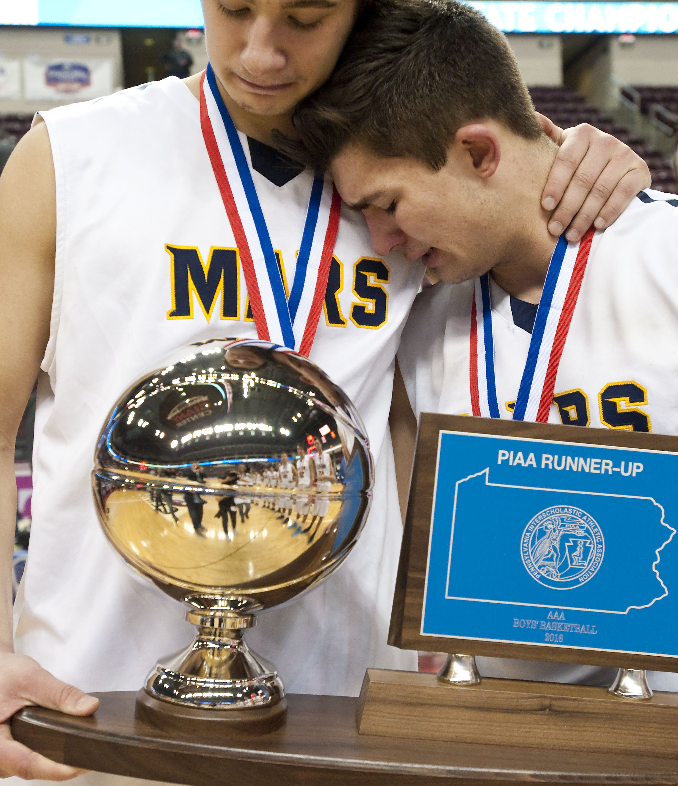 Mars Area's Christian Schmitt (23) rests on the shoulder of Mars Area's John Castello (3) with their runner-up trophy during the PIAA Class AAA boys basketball championship on Friday, March 18, 2016 at the Giant Center in Hershey, Pa. Neumann-Goretti won 99-66.