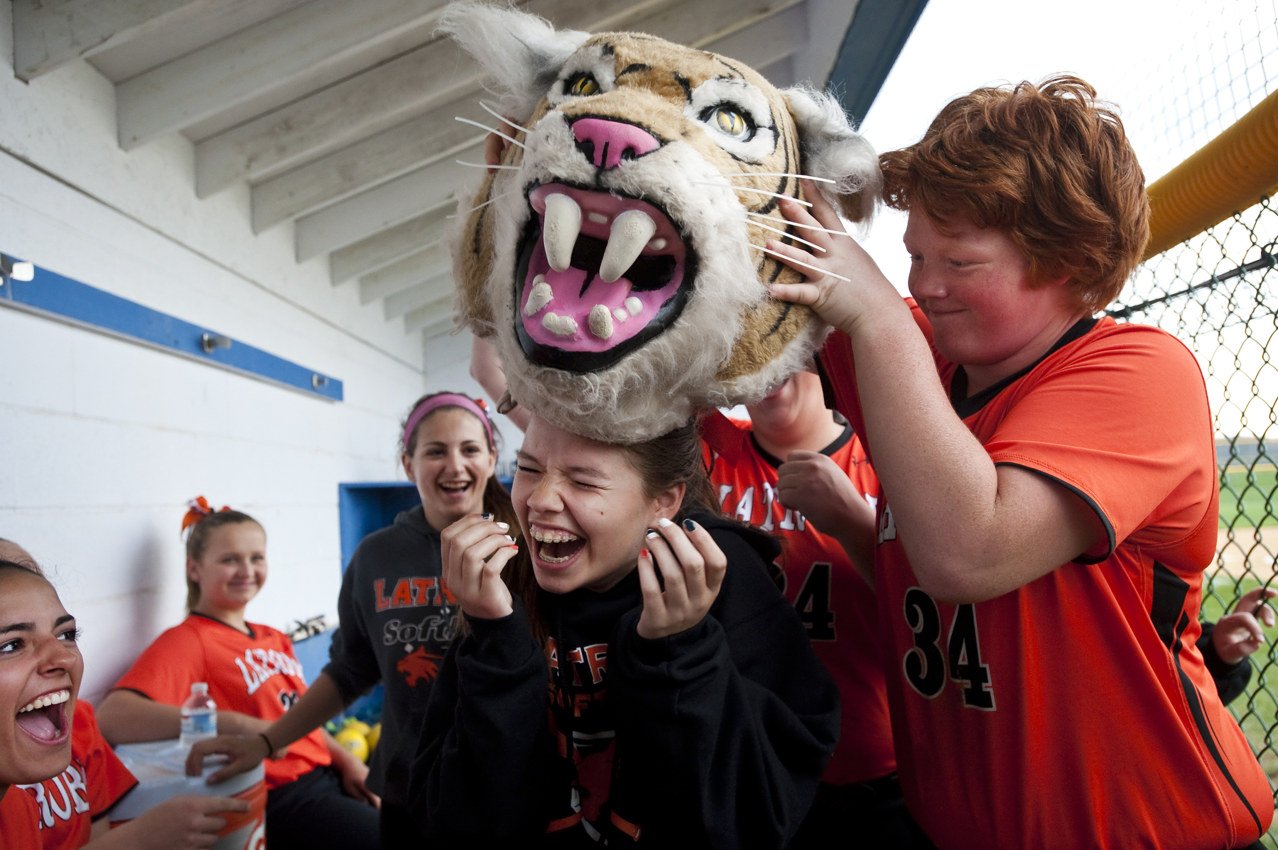 """Latrobe's Lauren Sigut is """"crowned"""" rock, paper, scissors champion by Morgan Schweizer while waiting out a rain delay during a softball game at Hempfield on Friday, April 22, 2016. Hempfield won 7-1."""