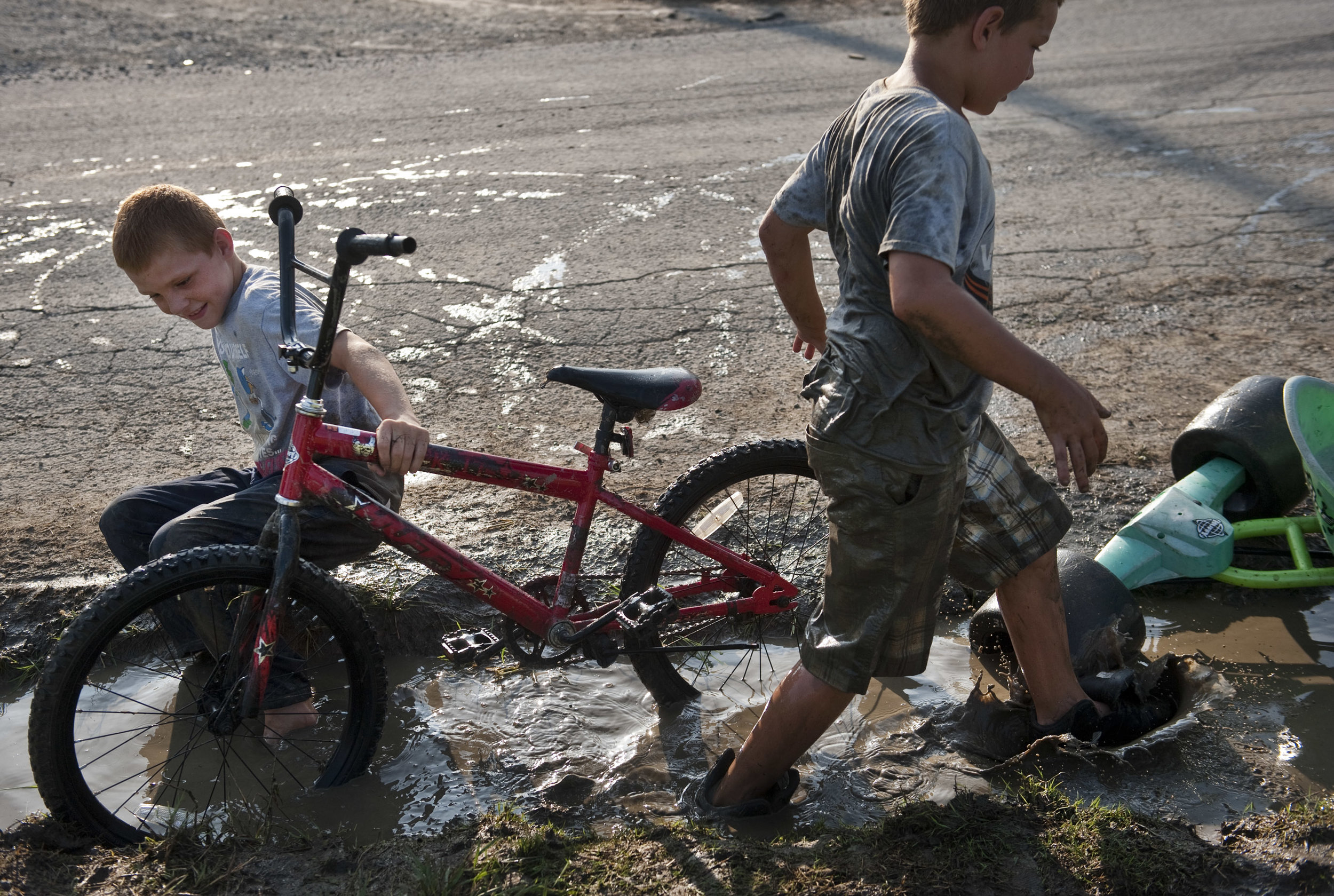 """Cammeron Bluey, 9 (left), plays with his brother Logan, 8, in the mud with their bikes while watching a District 31 American Legion baseball playoff game on Thursday, July 7, 2016 in Whitney. The brothers, who dubbed themselves """"The Dirtiest Kids in Whitney,"""" often play rough. """"He knocked my tooth out and when I got paid by the tooth fairy, I gave him 50 cents,"""" Cammeron said smartly. """"I tell him to do it. We've done it several times."""""""