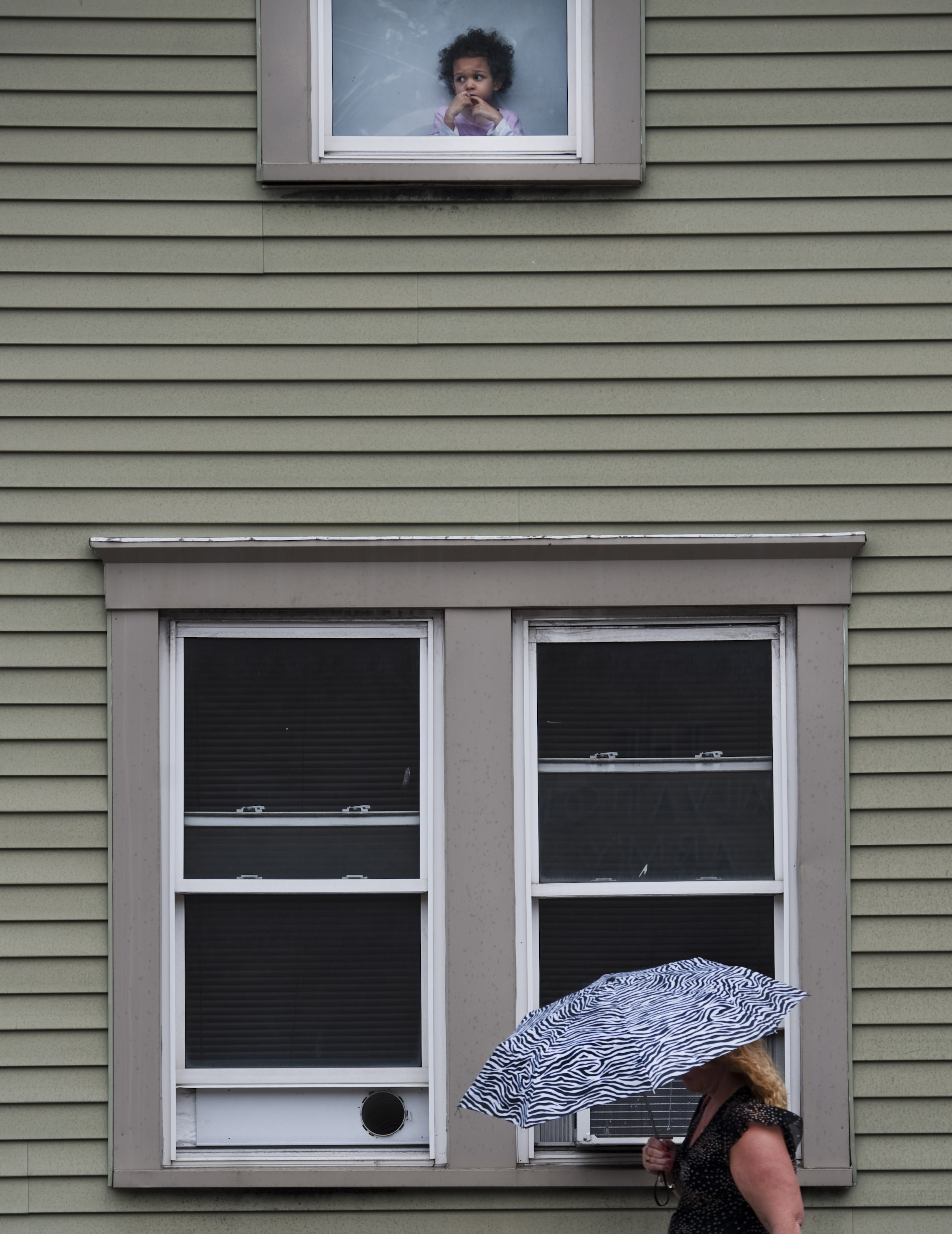 A young girl watches the rain fall as a pedestrian keeps herself dry along Otterman Street in Greensburg on Wednesday, Sept. 14, 2016.
