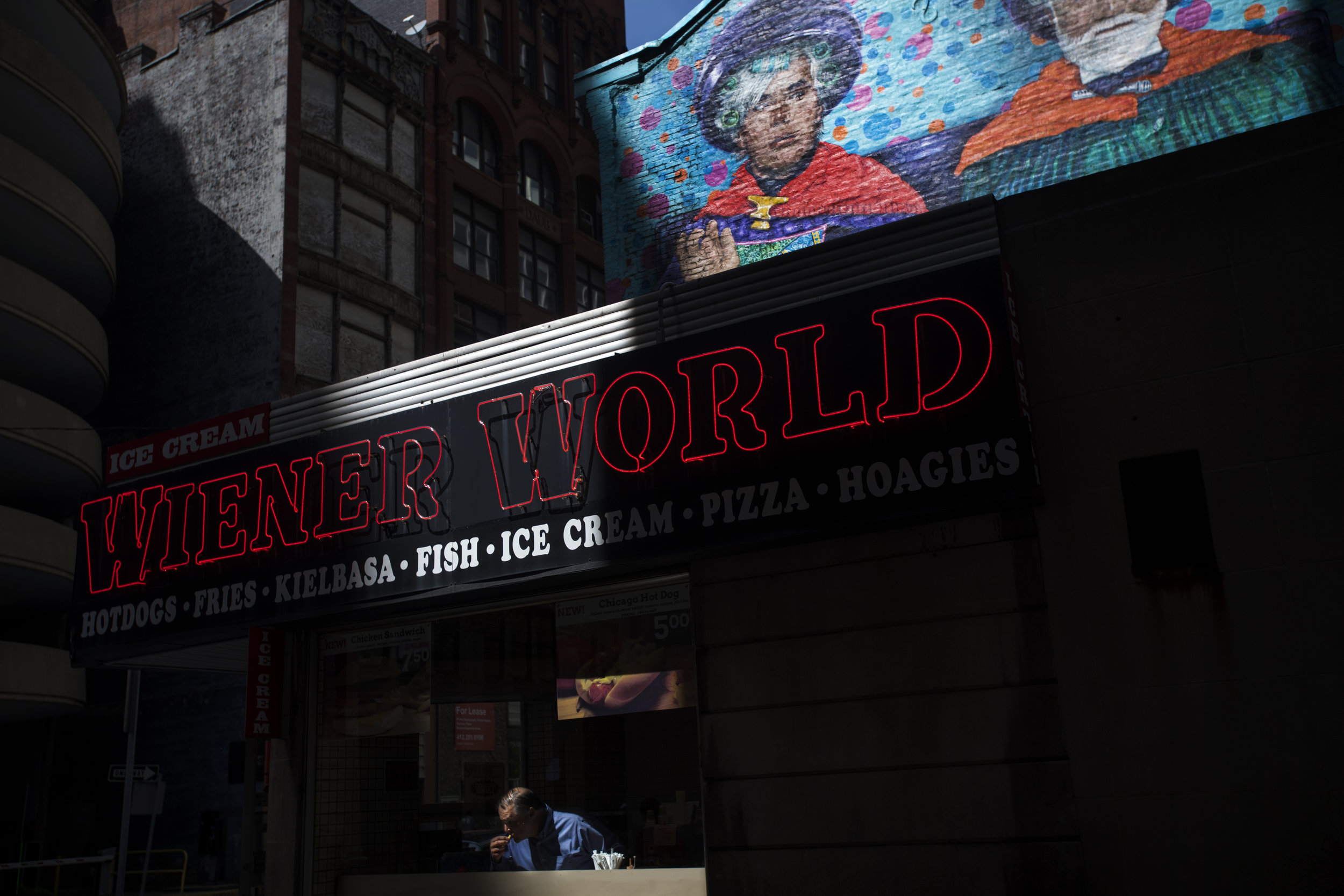 Sunlight shines on a patron eating inside Wiener World on Wednesday, April 26, 2017 as seen from Strawberry Way downtown. (Steph Chambers/Post-Gazette)