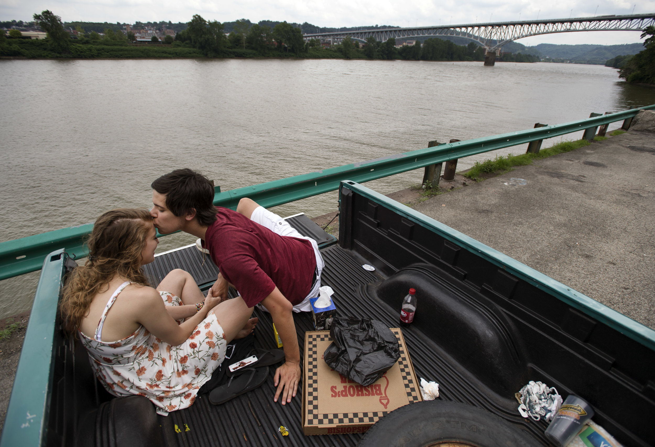"""Steel Valley High School sweethearts Angelica Good and Evan Lasek, both 18 of Munhall, enjoy pizza, lemonade and each other's company while picnicking on Thursday, June 22, 2017 along the Monongahela River near Duck Hollow Trail. The couple has been dating for two years and leaves for separate colleges on Saturday to begin summer classes. """"It'll be okay, babe,"""" said Lasek as he leaned in to kiss Good's forehead. Lasek will attend Penn State University for statistics and Good will attend Waynesburg University of forensic science. (Steph Chambers/Post-Gazette)"""