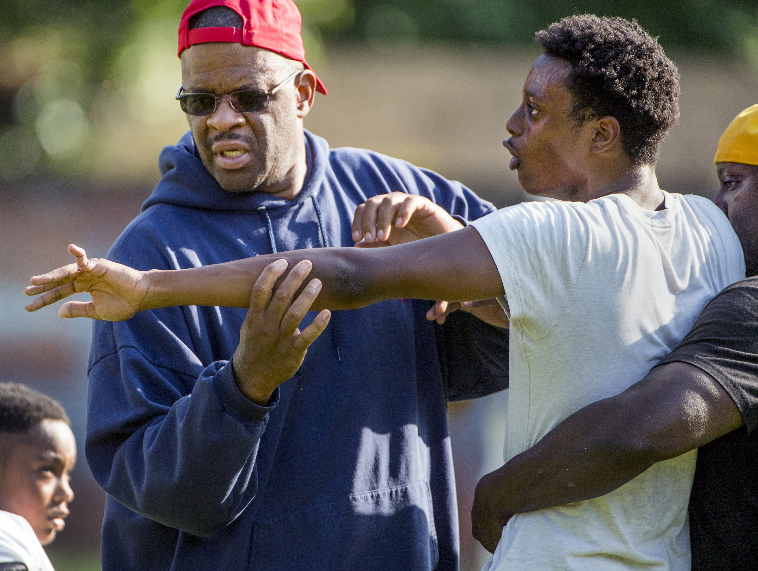 2017 TAB Westinghouse football coaches Eric Pennington and Ramon Robinson console Tariq Hamilton after he broke his finger catching ball during a preseason practice on Thursday, Aug. 3, 2017 at Westinghouse High School. (Steph Chambers/Post-Gazette)