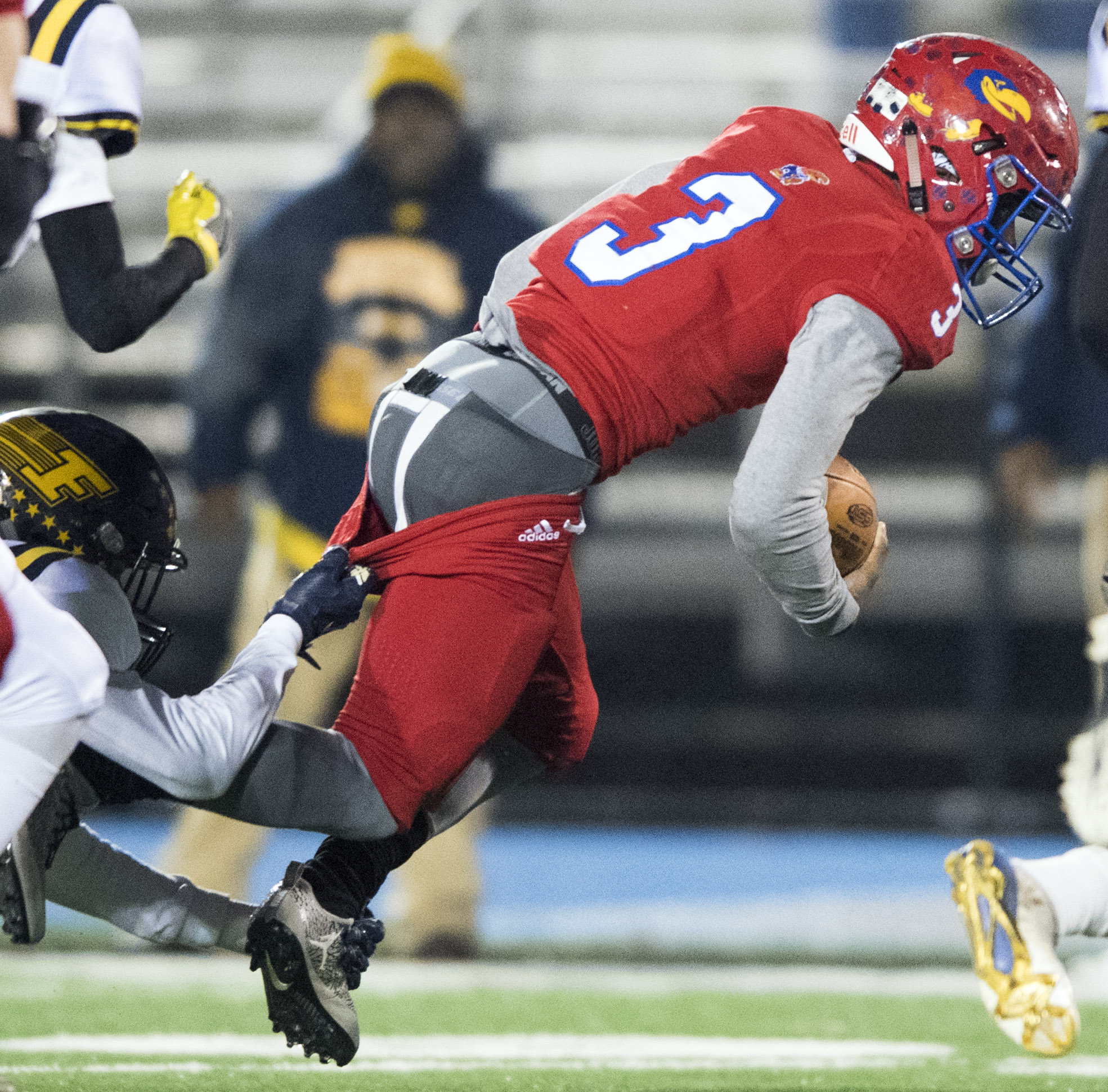 Jeannette's Robert Kennedy rushes as Farrell's Brian Hilton Jr. pulls his pants during the PIAA Class A semifinal on Friday, Dec. 1, 2017 at Seneca Valley High School. (Steph Chambers/Post-Gazette)