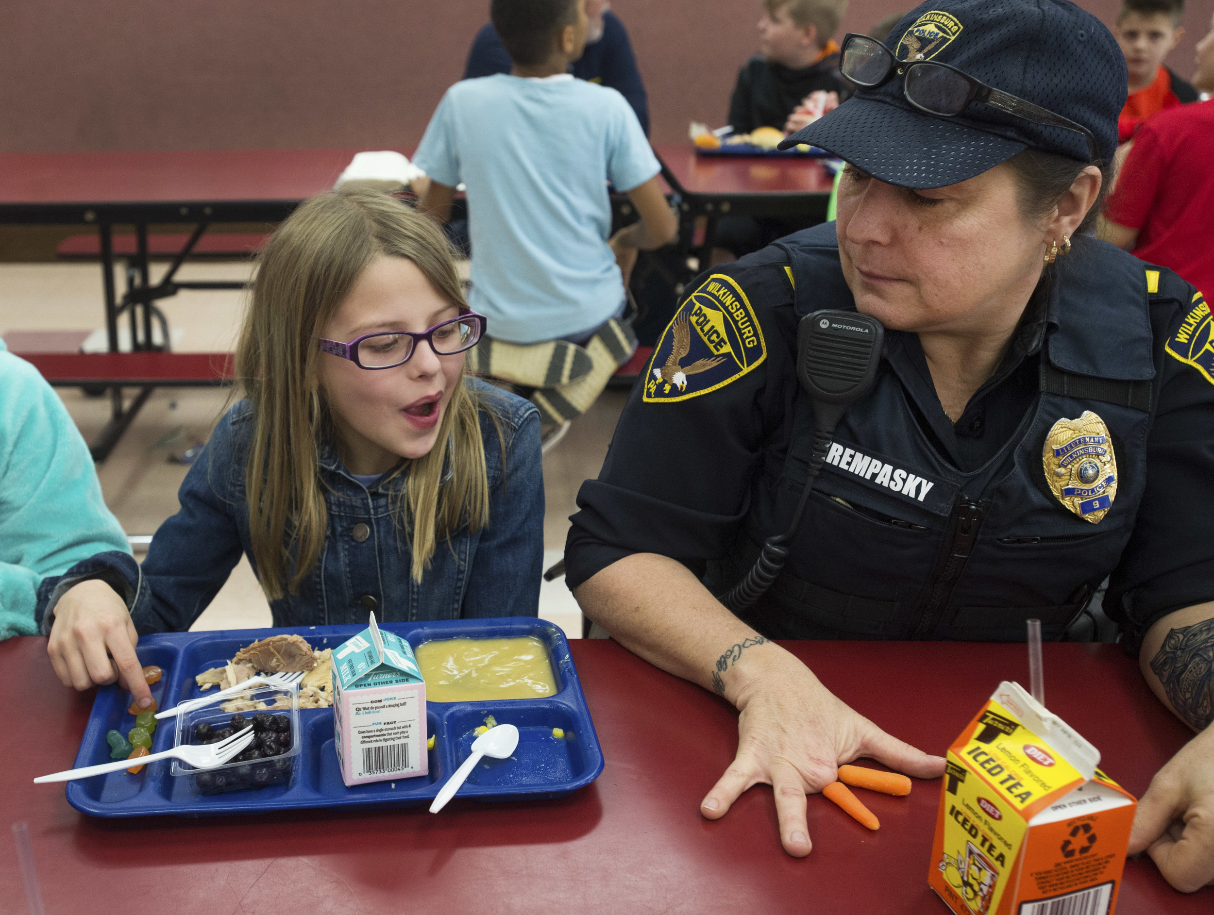 """Wilkinsburg Lt. Michele Krempasky shows 4th-grader Ava her """"carrot fingers"""" during a Hero Luncheon at Sloan Elementary School in Murrysville, Pa. on Wednesday Feb. 22, 2017. Krempasky lost her fingers in a saw accident. Despite the injury and possible retirement, she learned to shoot her gun with her left hand. (Steph Chambers 