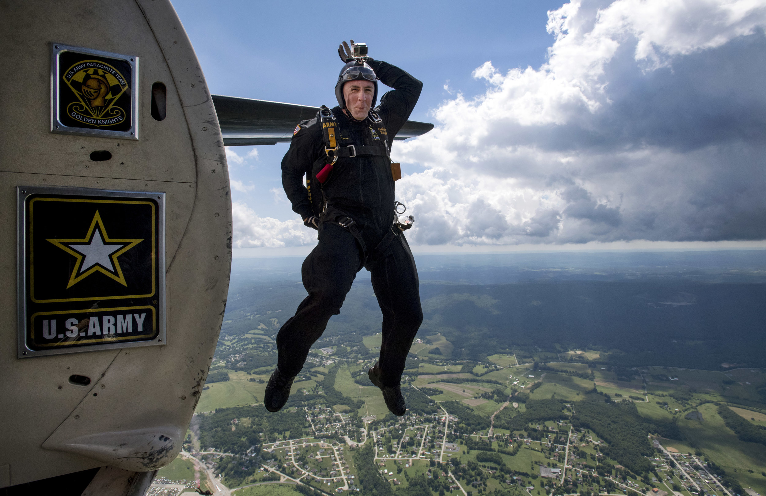 Sgt. 1st Class Brian Karst, of the United States Army Parachute Team Golden Knights and of Vancouver, Washington, protects his head as he leaps out of an airplane during the Shop 'n Save Westmoreland County Airshow on Sunday, June 25, 2017 at Arnold Palmer Regional Airport in Unity. (Steph Chambers/Post-Gazette)