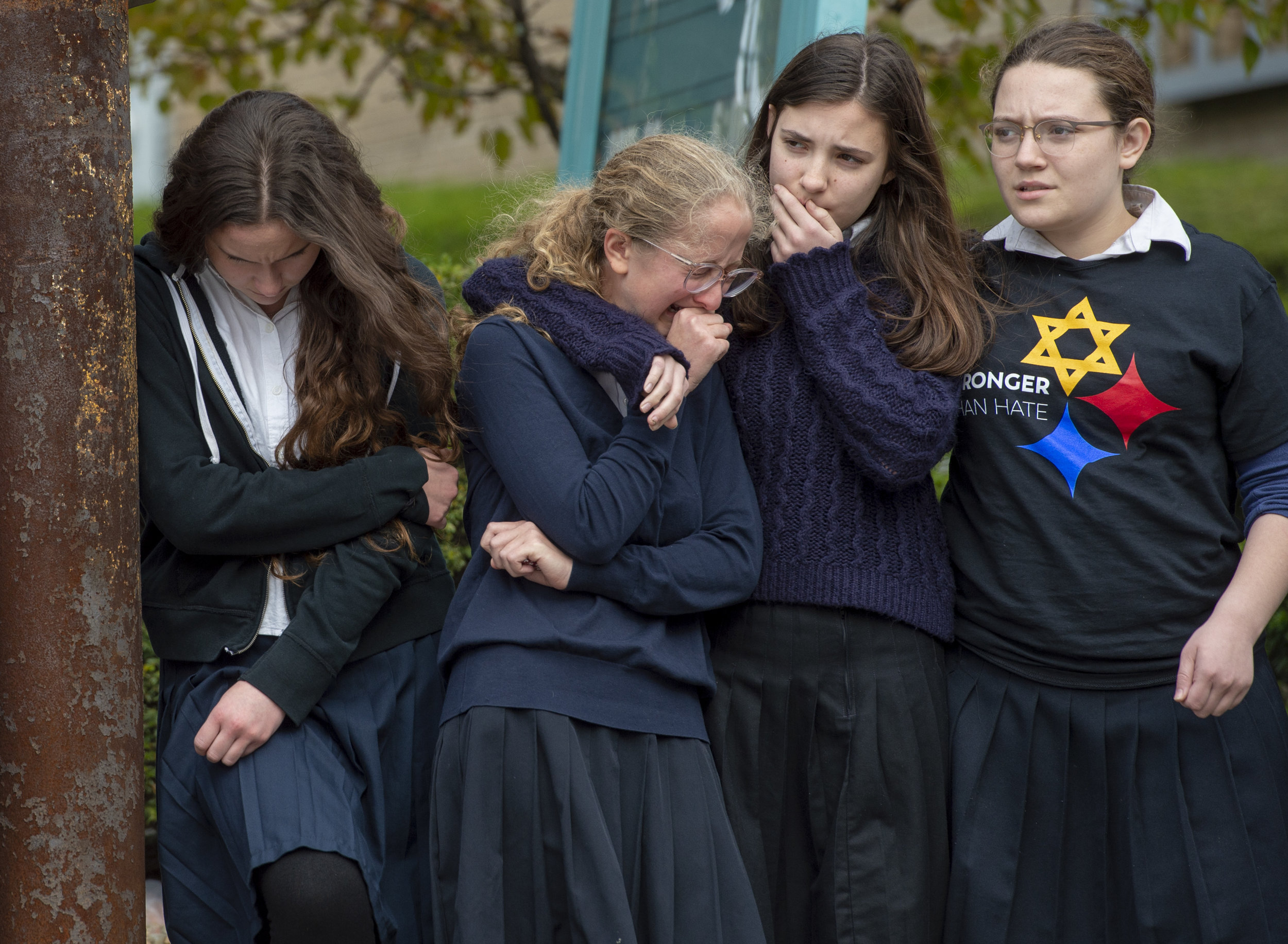 Yeshiva School students Batsheva Ezagui, Batya Deitsch, Esther Rivka Shkedi, Tzipporah Shkedi watch a funeral procession for Dr. Jerry Rabinowitz drive along Forbes Avenue as it heads toward Homewood Cemetery, on Tuesday, Oct. 30, 2018, in Squirrel Hill. Eleven people were killed and six were wounded, including four police officers, after a mass shooting at Tree of Life Congregation on Saturday, Oct. 27, 2018, in Squirrel Hill. (Steph Chambers/Post-Gazette)