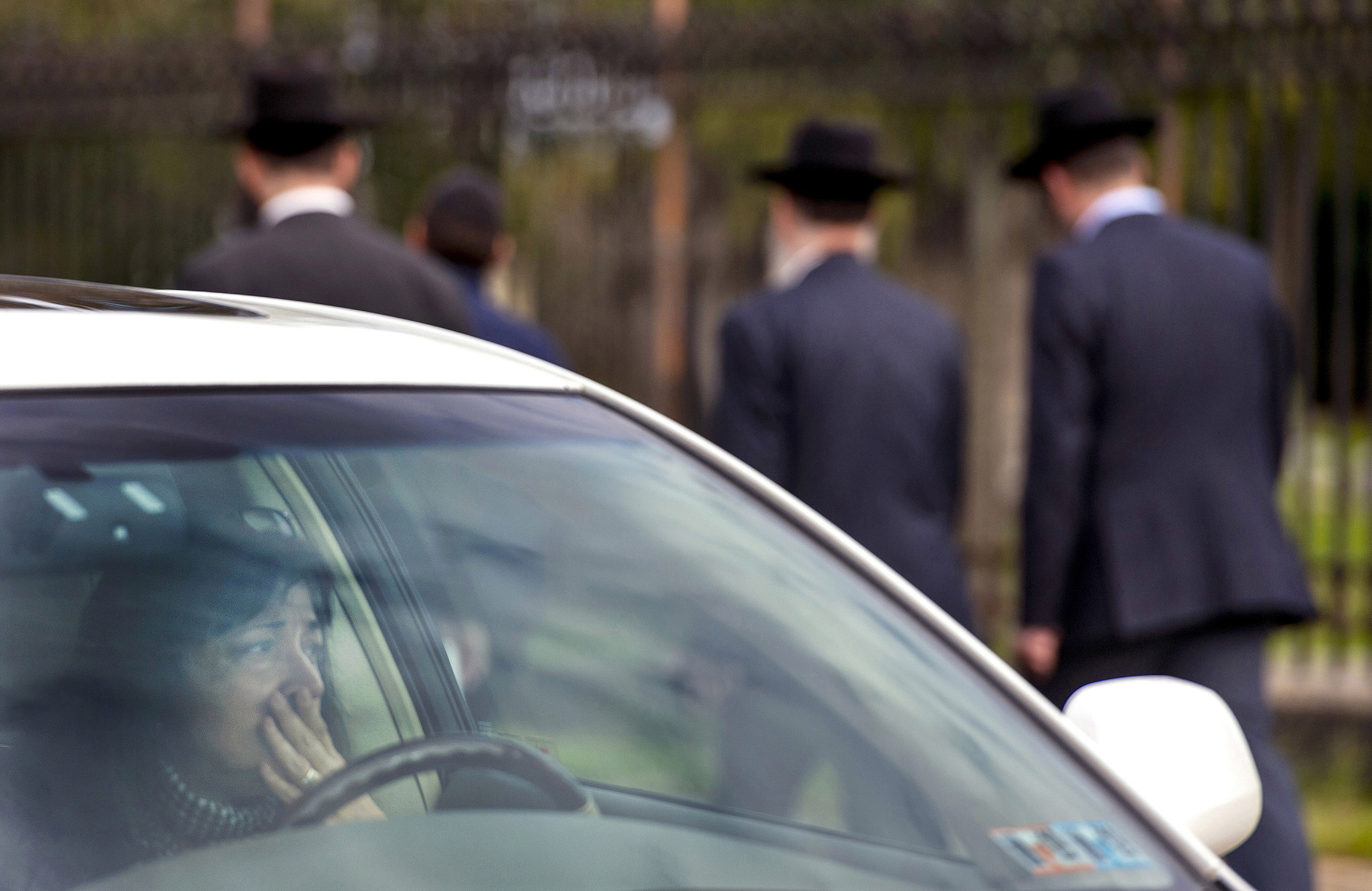 A woman in her car pauses as the hearse carrying Dr. Jerry Rabinowitz heads toward Homewood Cemetery along South Dallas Avenue, on Tuesday, Oct. 30, 2018, in Squirrel Hill. Eleven people were killed and six were wounded, including four police officers, after a mass shooting at Tree of Life Congregation on Saturday, Oct. 27, 2018, in Squirrel Hill.