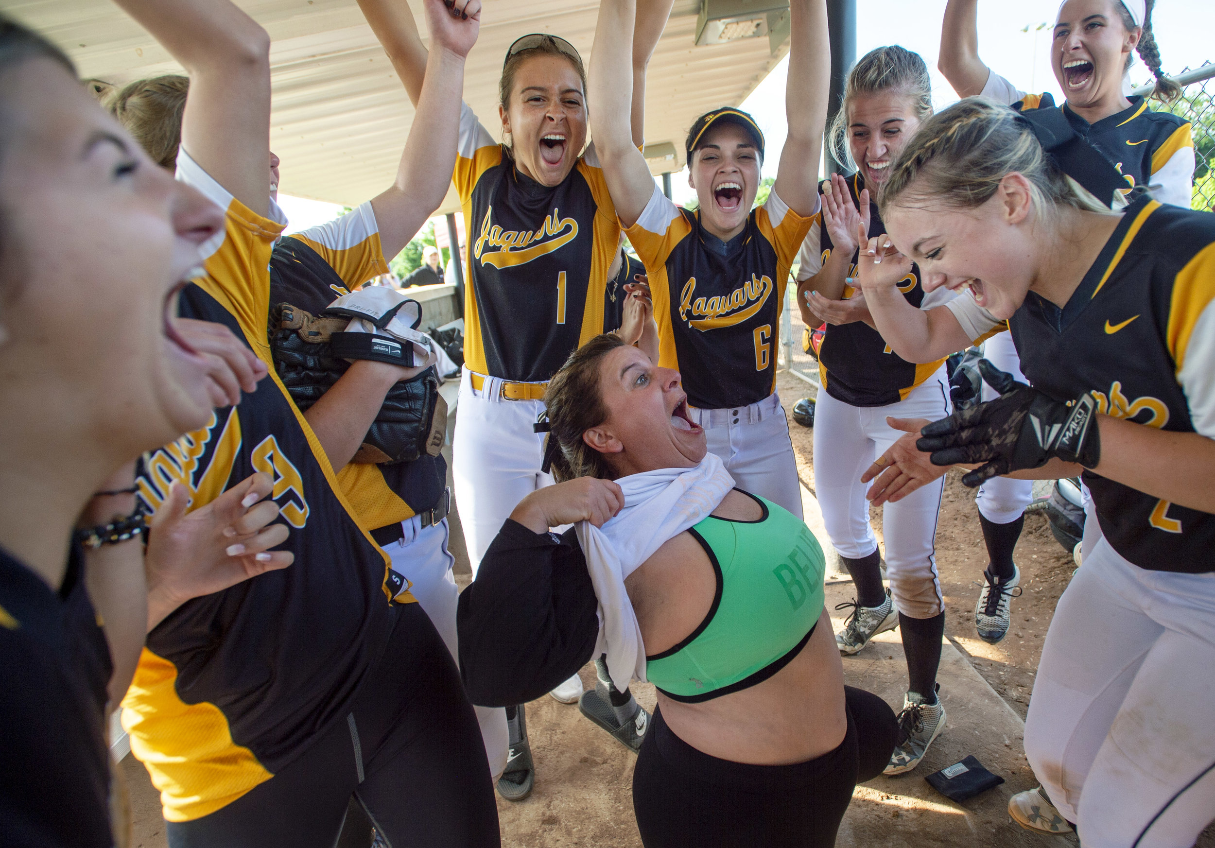 """Thomas Jefferson head softball coach Heidi Karcher shows her """"believe"""" lucky sports bra to her players after beating Albert Gallatin 2-0 in 8 innings during the WPIAL Class 5A softball semifinal on Wednesday, May 23, 2018, at Boyce Mayview Park. (Steph Chambers/Post-Gazette)"""