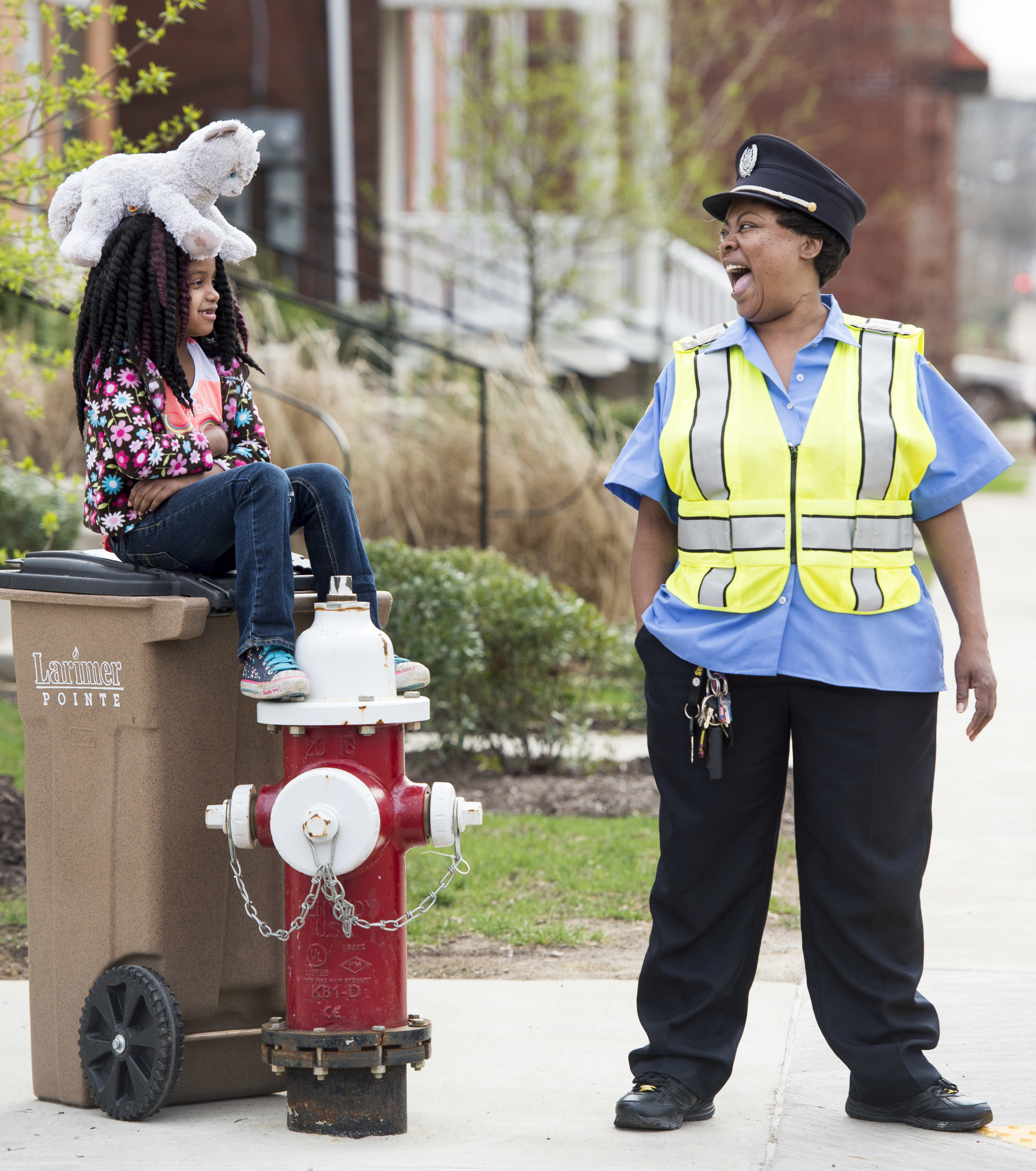 """City of Pittsburgh crossing guard Carla Harris (right) laughs with Rhavyn Doubt, 7, and Doubt's stuffed animal """"Fluffy"""" as Doubt waits with her on Wednesday, April 18, 2018 at the corner of Meadow Street and Larimer Avenue in Larimer. """"She's a sweetie, and she keeps me company,"""" Harris said of Doubt, who lives nearby but likes to sit with her at the intersection on a regular basis. """"I'm like a godmother to the kids because I am here every day watching over them and protecting them."""" (Steph Chambers/Post-Gazette)"""
