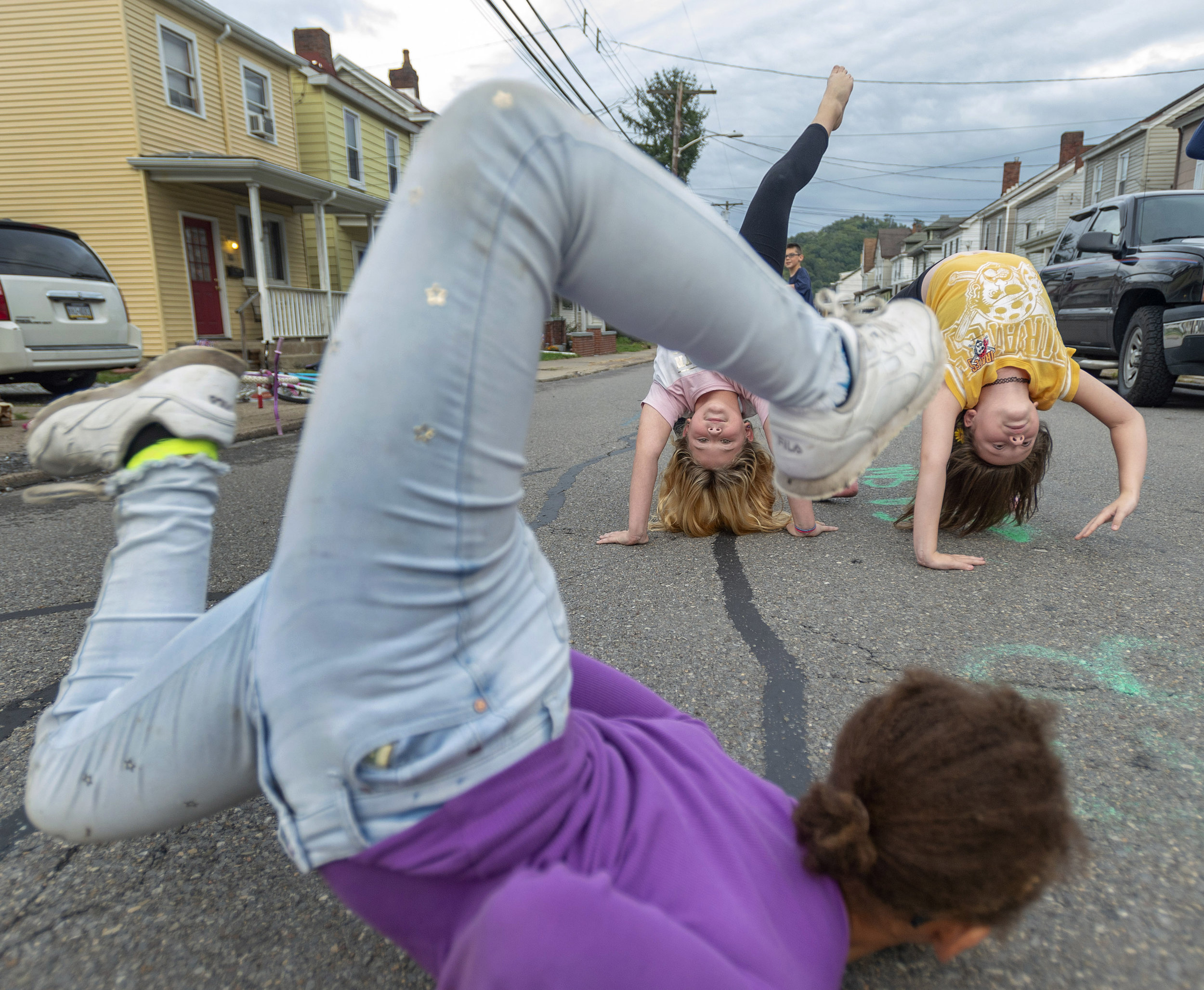 """Chianne Corniffe, Callie Rector and Graci Ricci, all 10, practice their gymnastics on Wednesday, Sept. 26, 2018, along Dewey Street, or as the girls refer to it as """"the party street,"""" in Etna. (Steph Chambers/Post-Gazette)"""