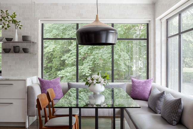 A once dark and gloomy eating area is now full of light, letting in nature. It's a step away from the family's outdoor terrace and pool area.