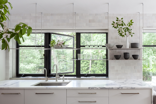 This close-up image shows the glass shelving that hangs over both windows and walls, the Moroccan tiles, and the simple cabinet surfaces.