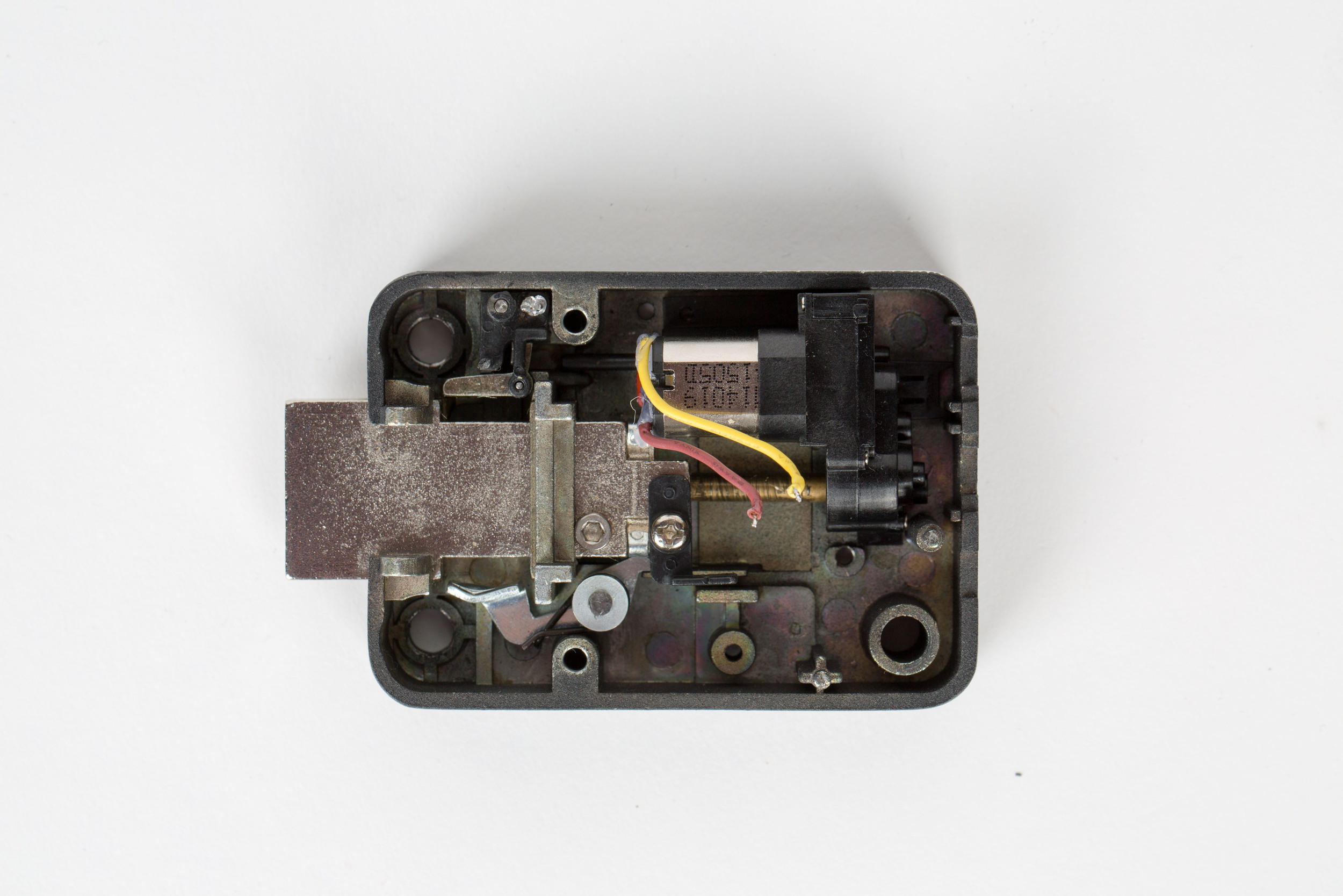 The lock body is the only mechanical part of the system. It is composed of a DC motor and bolt. If 5 volts is applied across the red and yellow wires shown, the DC motor will retract the bolt and allow the security container to be opened.