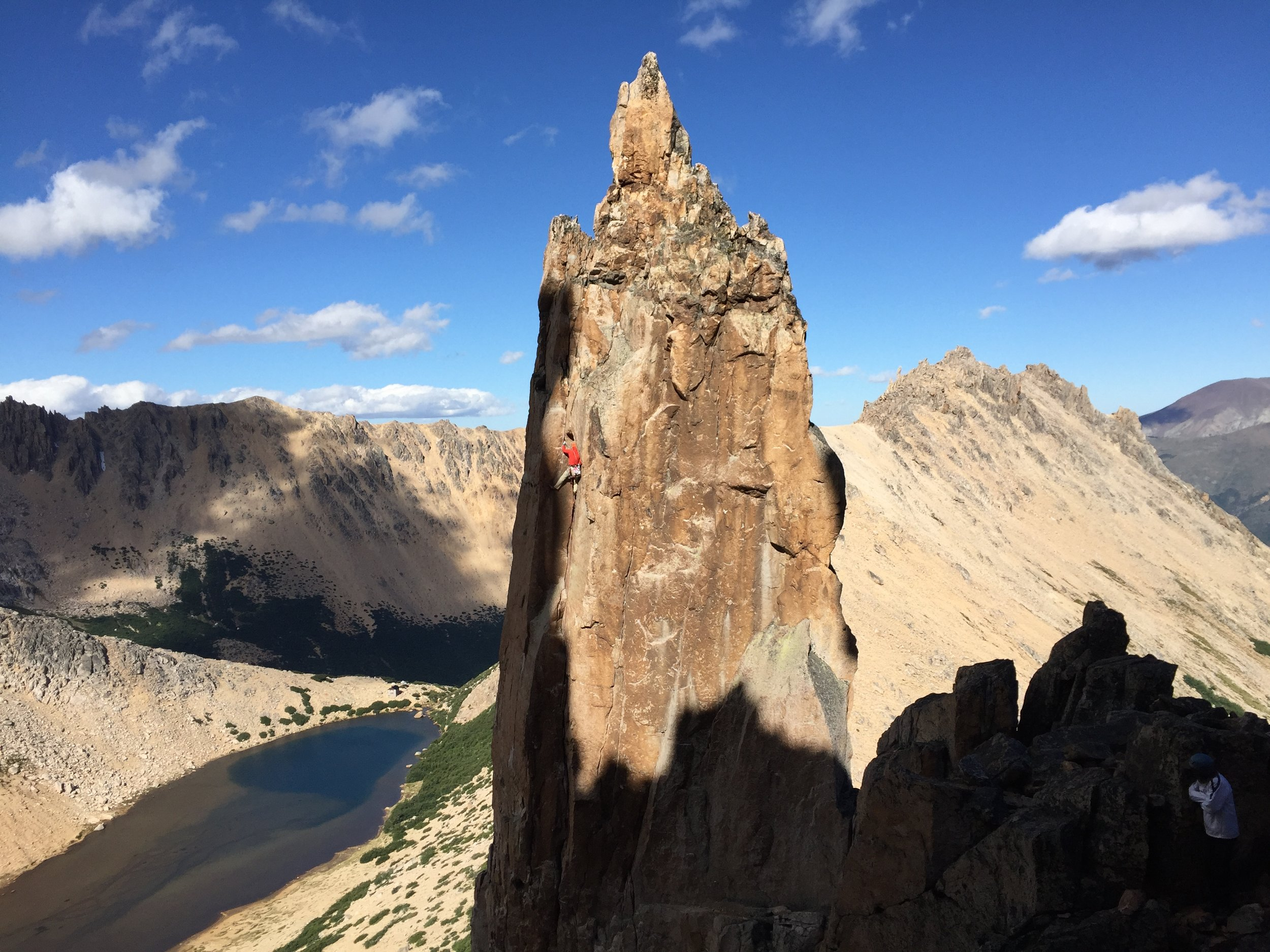 Karah on Del Diedro (5.9) with Laguna Toncek and a tiny Refugio Frey in the background