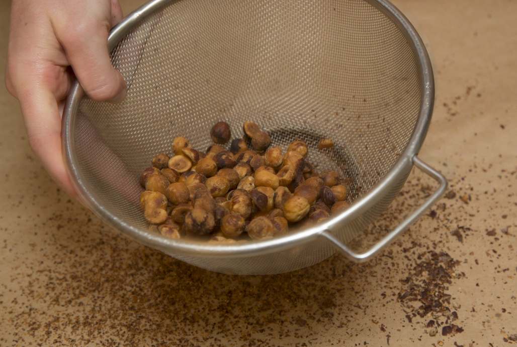 Gently toss the hazelnuts in a sieve to separate smaller bits of skin.
