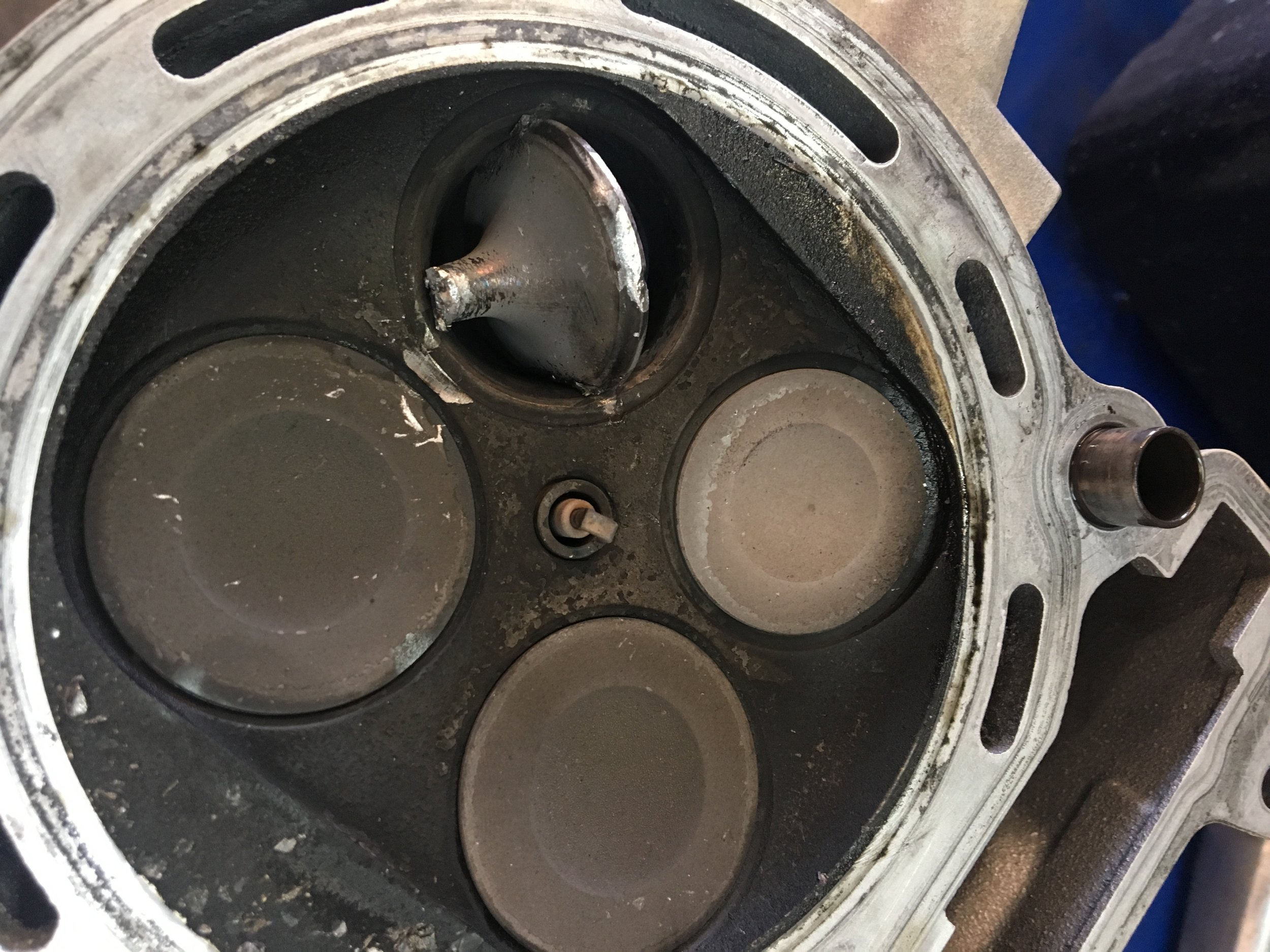We believe what happened is that the bike was run without coolant and that exhaust valve got really hot and seized in the guide causing the piston to hit it, break it and then jam it into the head.  Not a good day!