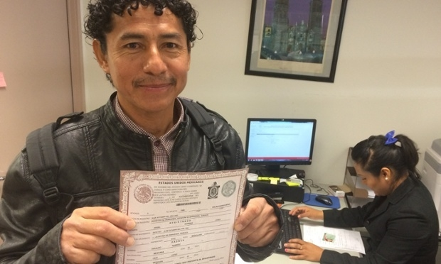 Ángel Ramirez shows his newly printed birth certificate.     Photograph: The Guardian