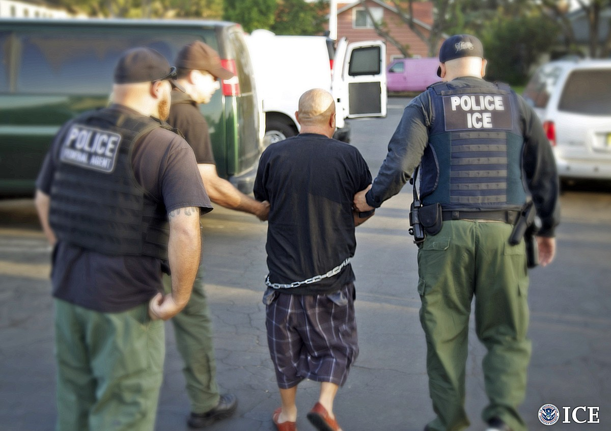 U.S. Immigration and Customs Enforcement agents take a man into custody during an immigration sweep in Ontario in San Bernardino County, Oct. 14, 2014. ICE provided the photo.