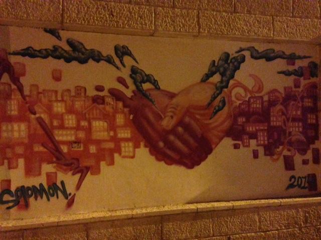 Street art depicting hands grasping in Jerusalem