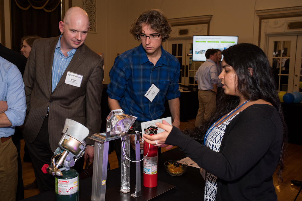 ARE fellow Emily Ghosh walks two people through Marigold Power's thermophotovoltaic demonstration.