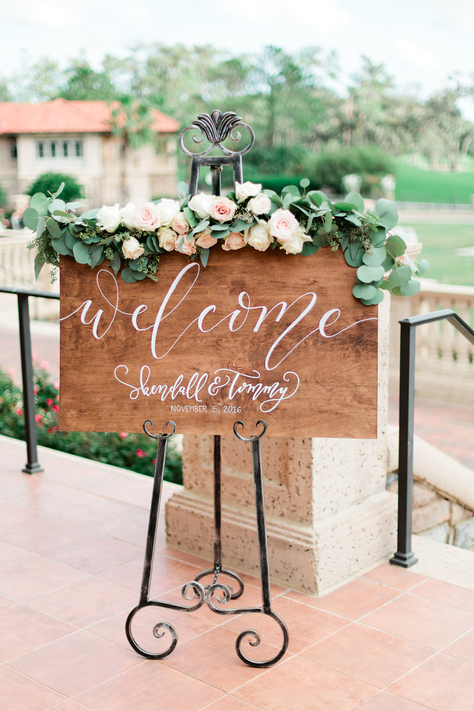 Wooden welcome sign with calligraphy and garland with blush and ivory flowers  Blush Wedding at TPC Sawgrass Wedding Ponte Vedra Beach  Jacksonville Wedding Planner Blue Ribbon Weddings  Jacksonville Wedding Photographer Debra Eby Photography  Wedding Ceremony & Reception at TPC Sawgrass Jacksonville