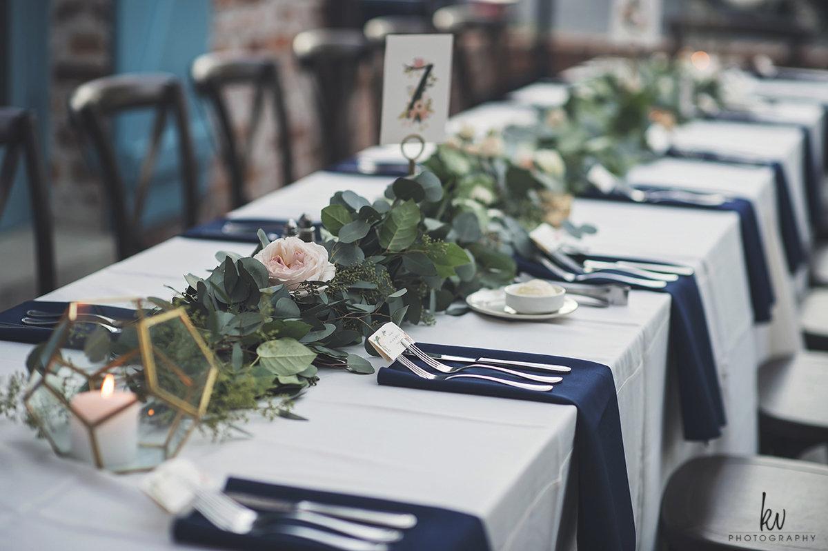 Navy linen napkins, blush roses, gold terrariums