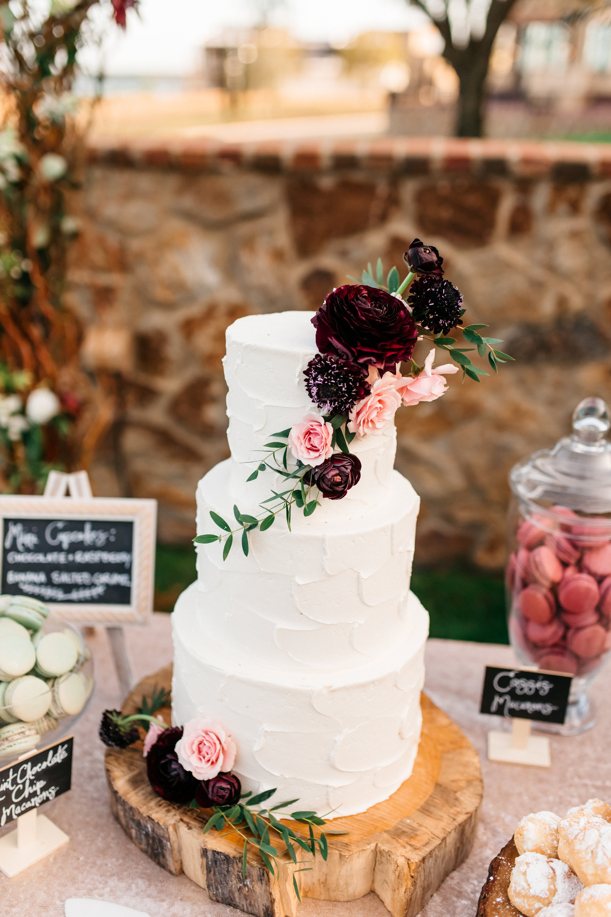 Classic three tier wedding cake with blush and deep red florals