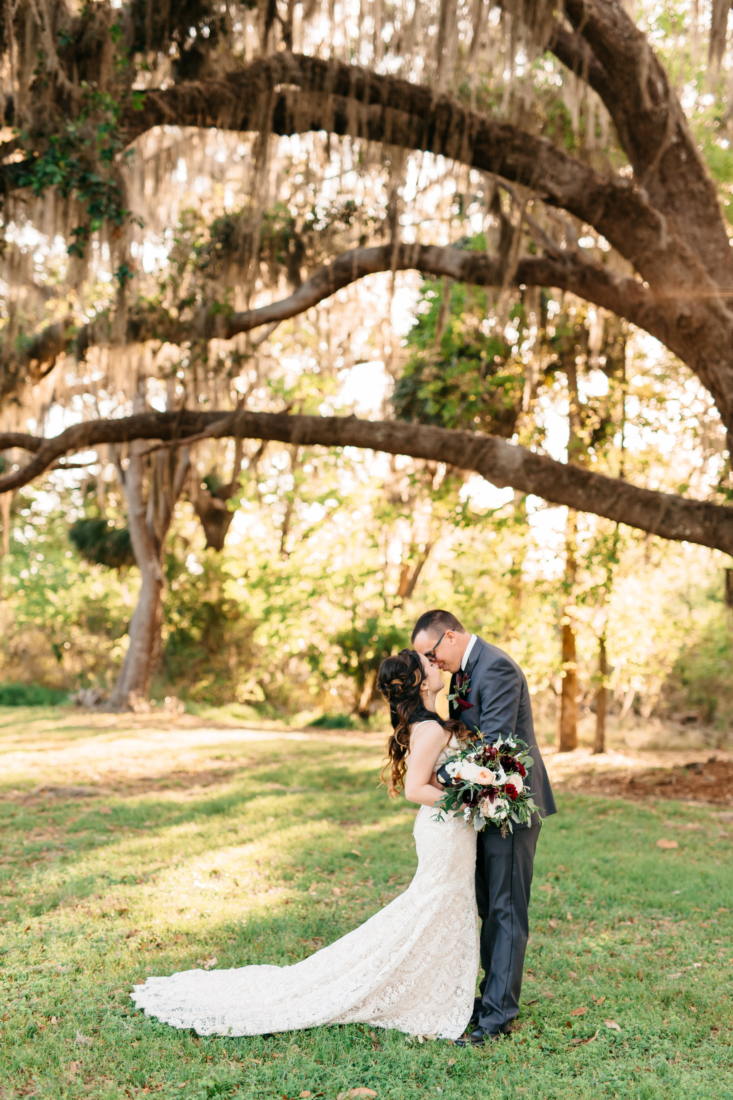 The newly weds share a kiss under the Cypress Tree, Bella Collina Weddings