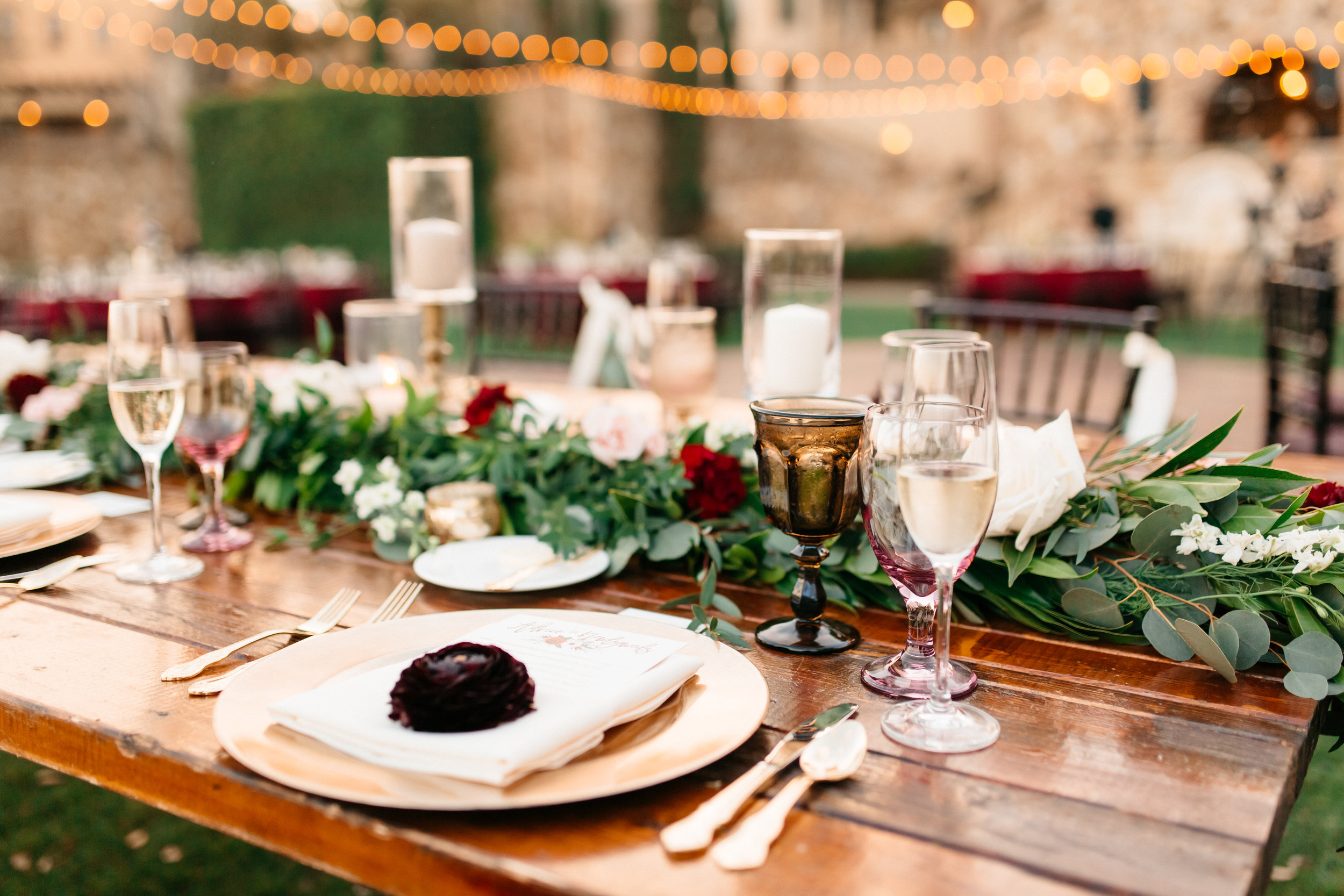 Romantic reception with larger wooden farm tables, garlands filled with roses and candles