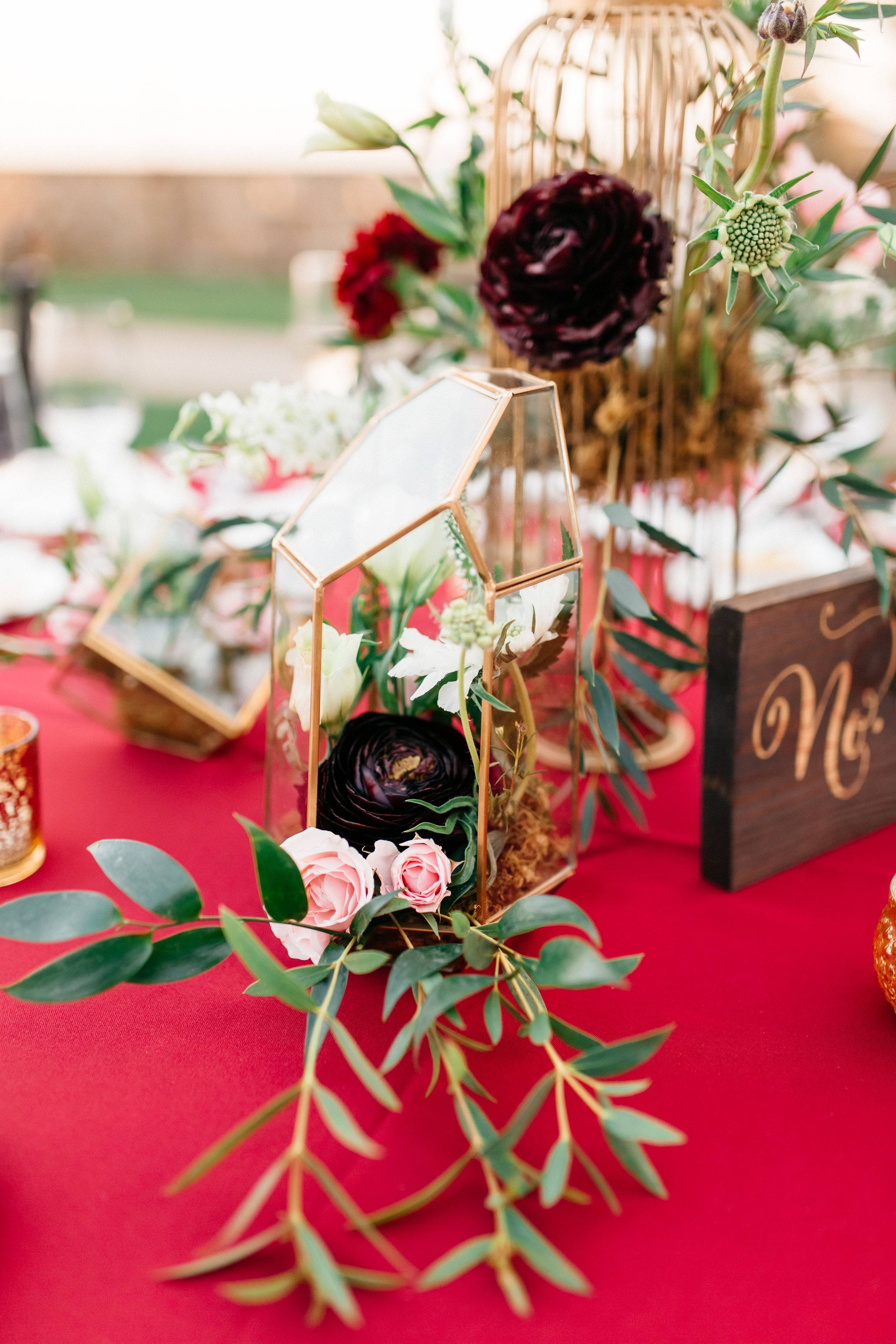 Gold terrariums filled with deep red and blush spray roses