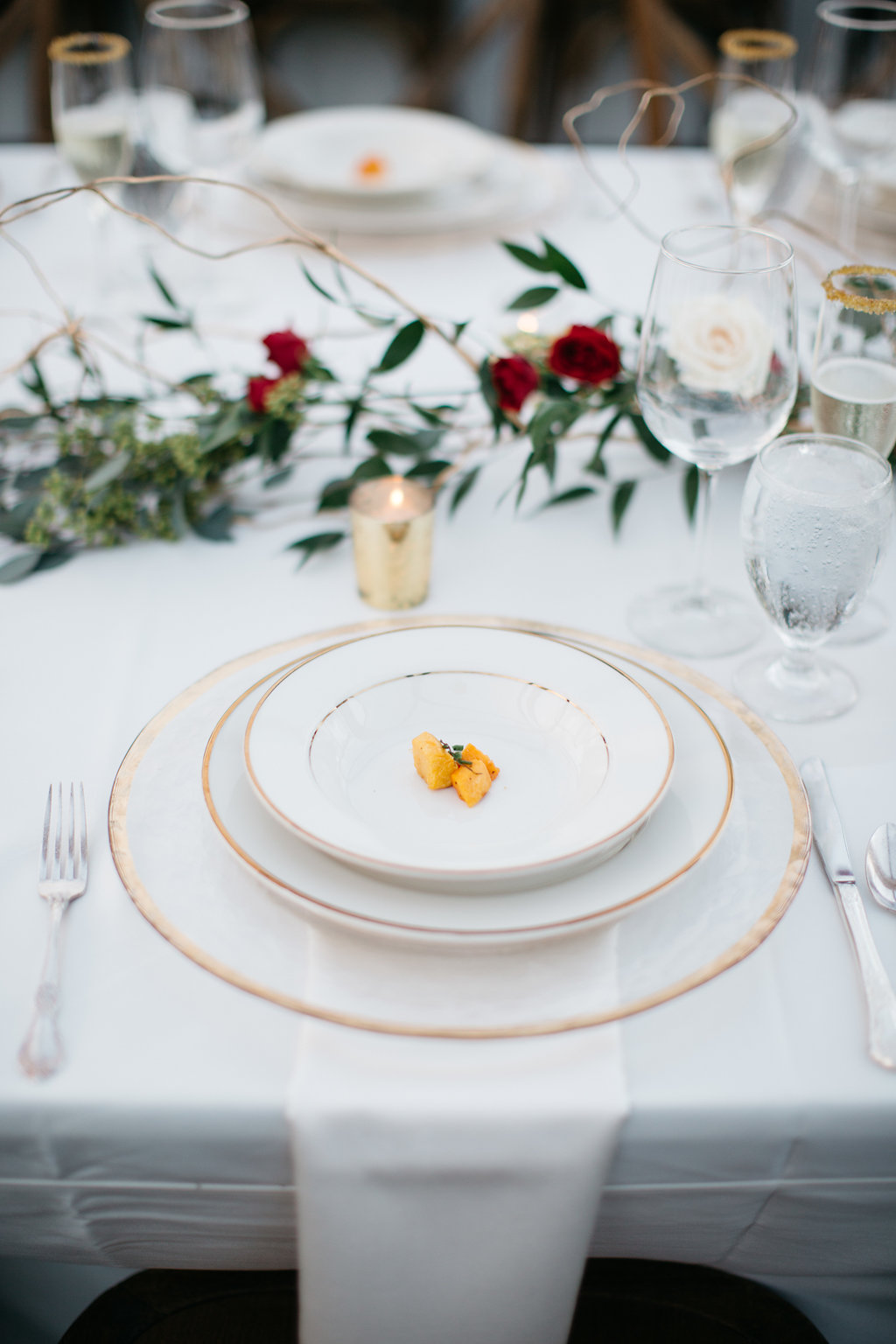 Gold rimmed dishware to complete the holiday themed wedding reception