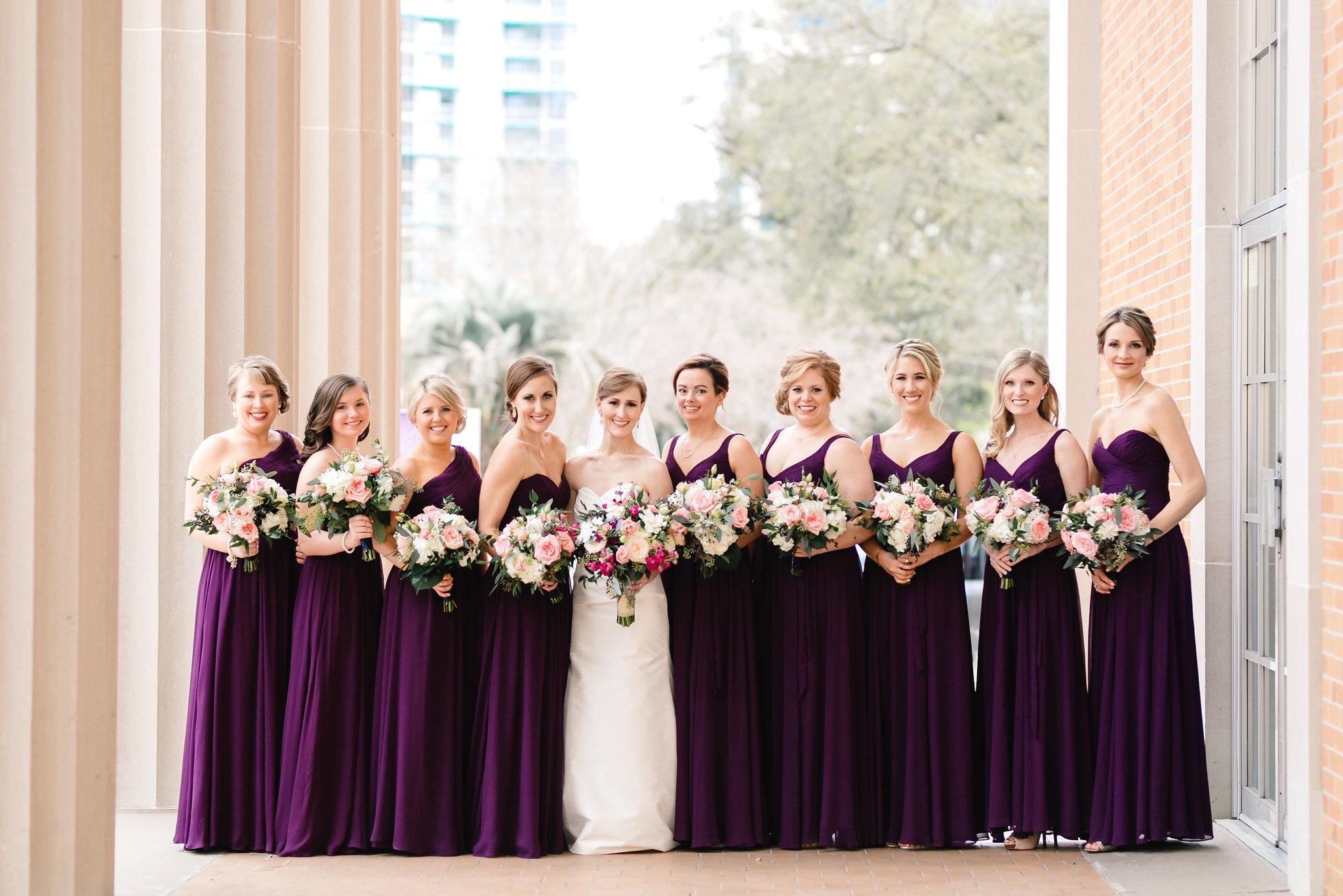 Bride with her bridesmaids in deep plum dresses