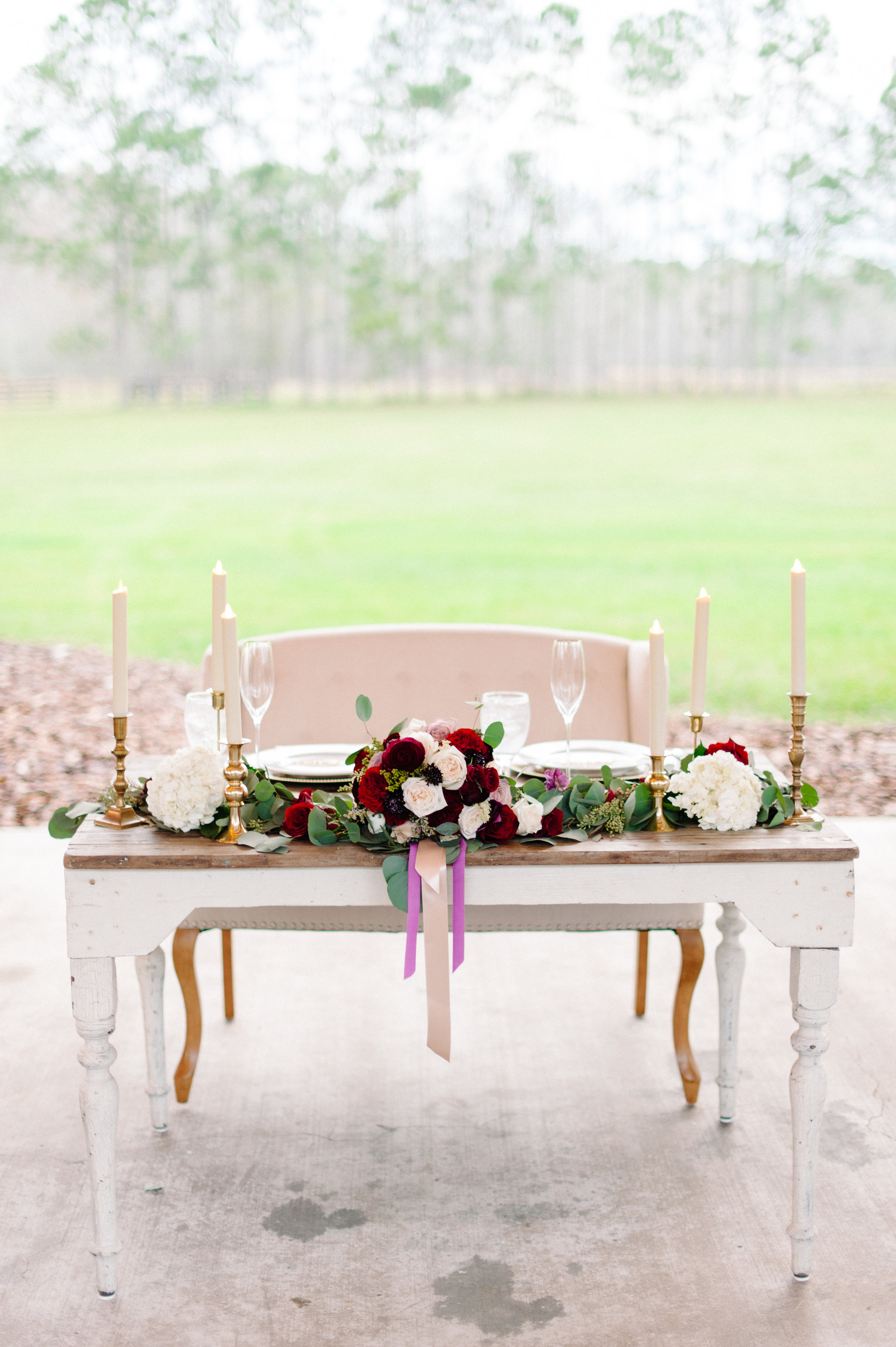 Sweetheart table with elegant candlesticks, highlighting the bridal bouquet