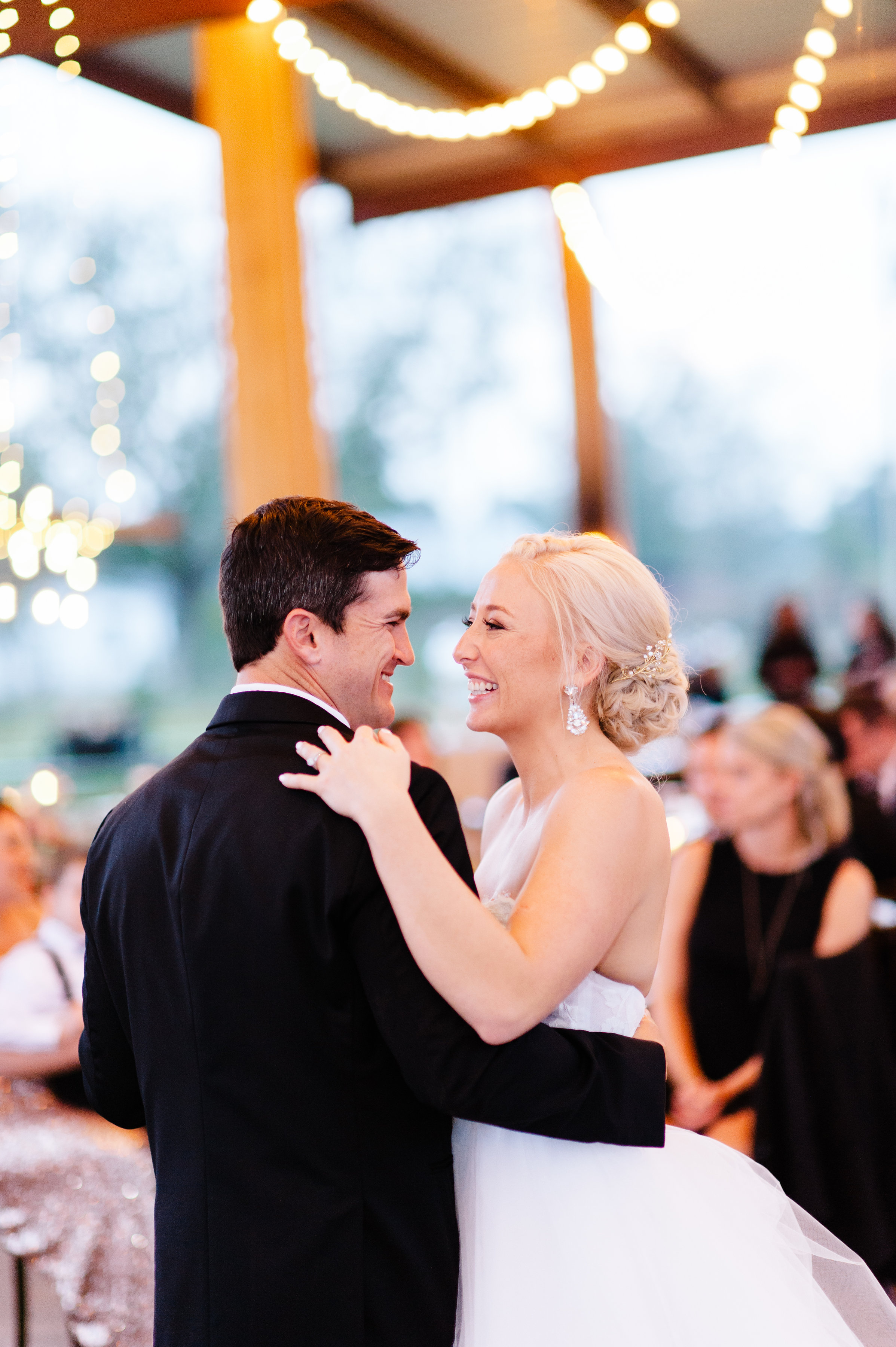 They share their first dance under romantic market lighting