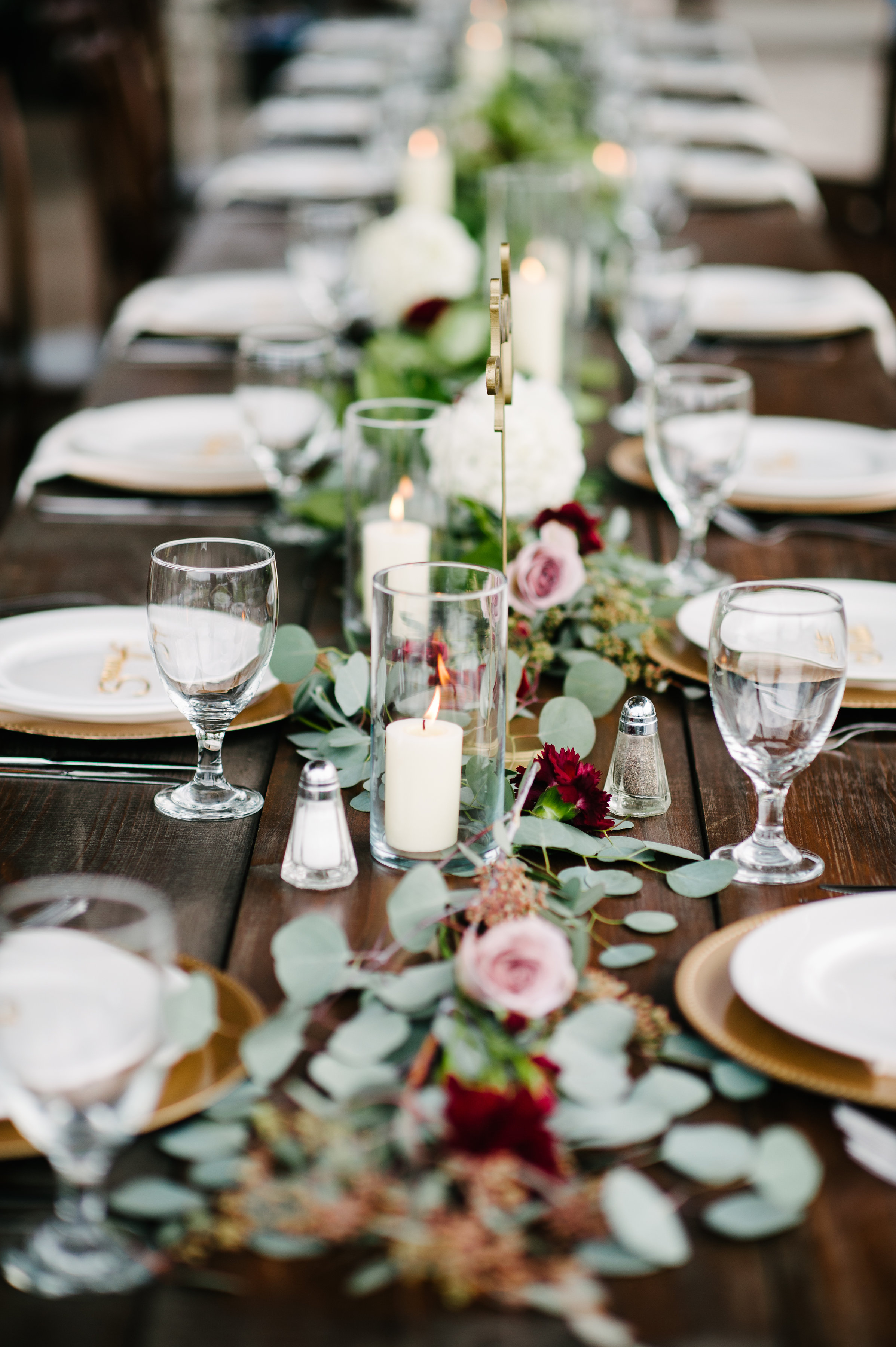 Reception banquet tables lined with candles, blush roses and greenery