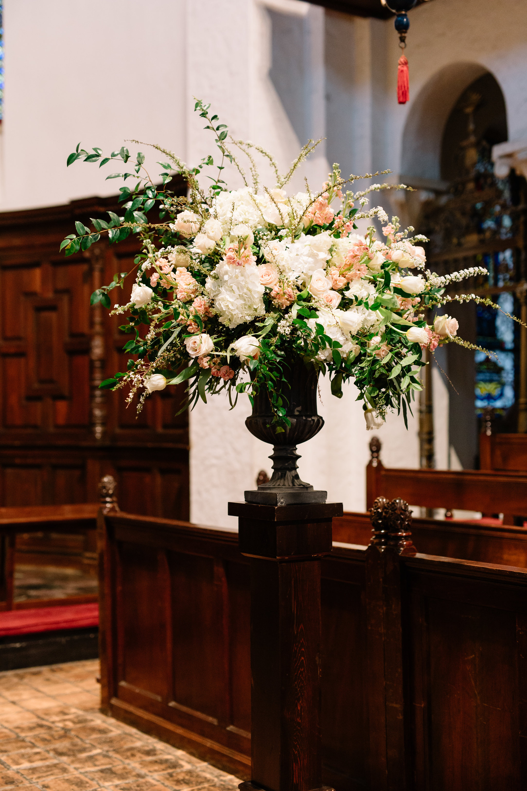 Ceremony floral arrangement of ivory hydrangea, blush roses and sprigs of greenery