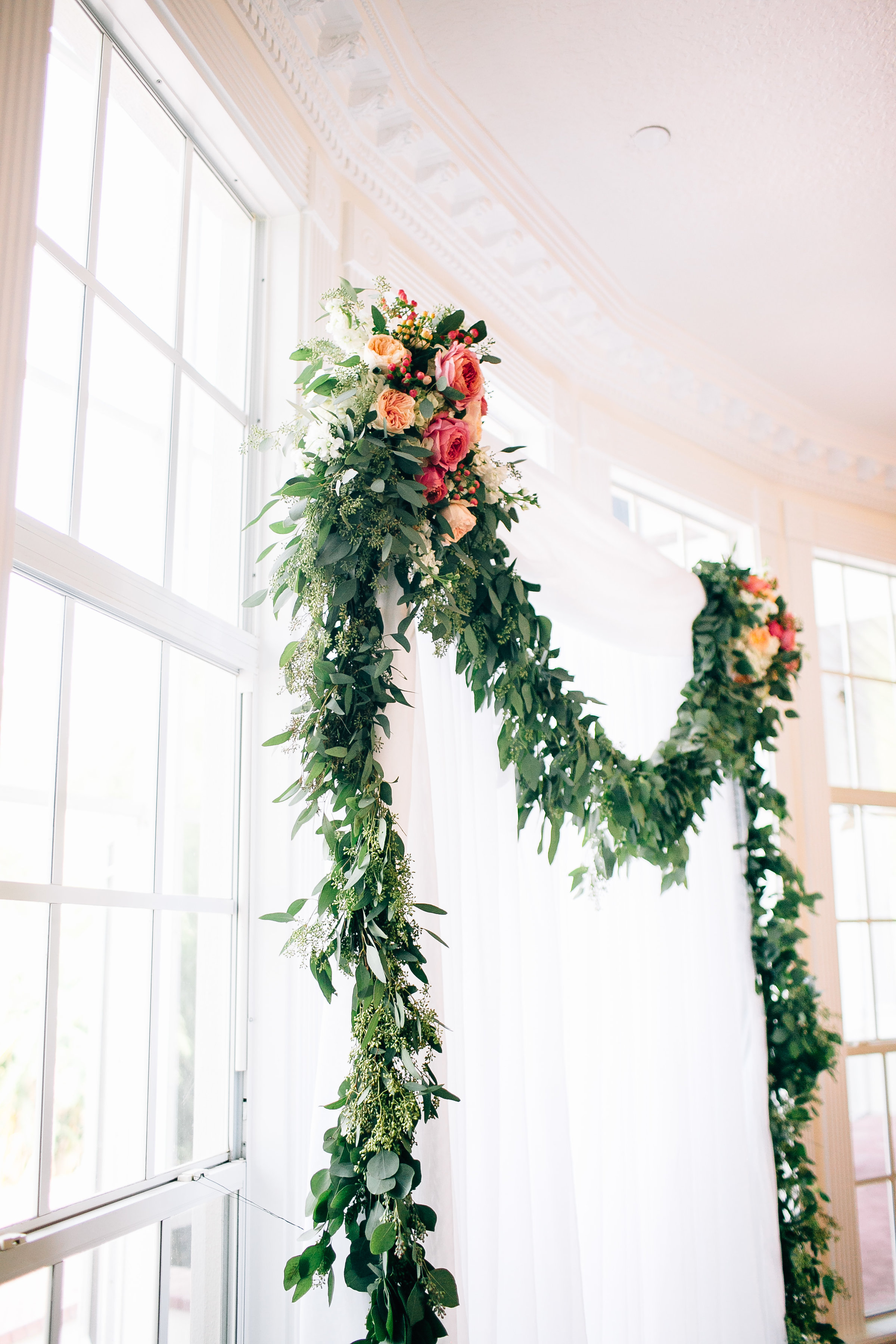 Eucalyptus floral arch with draping indoor ceremony at Luxmore Grande, Orlando Wedding Planner