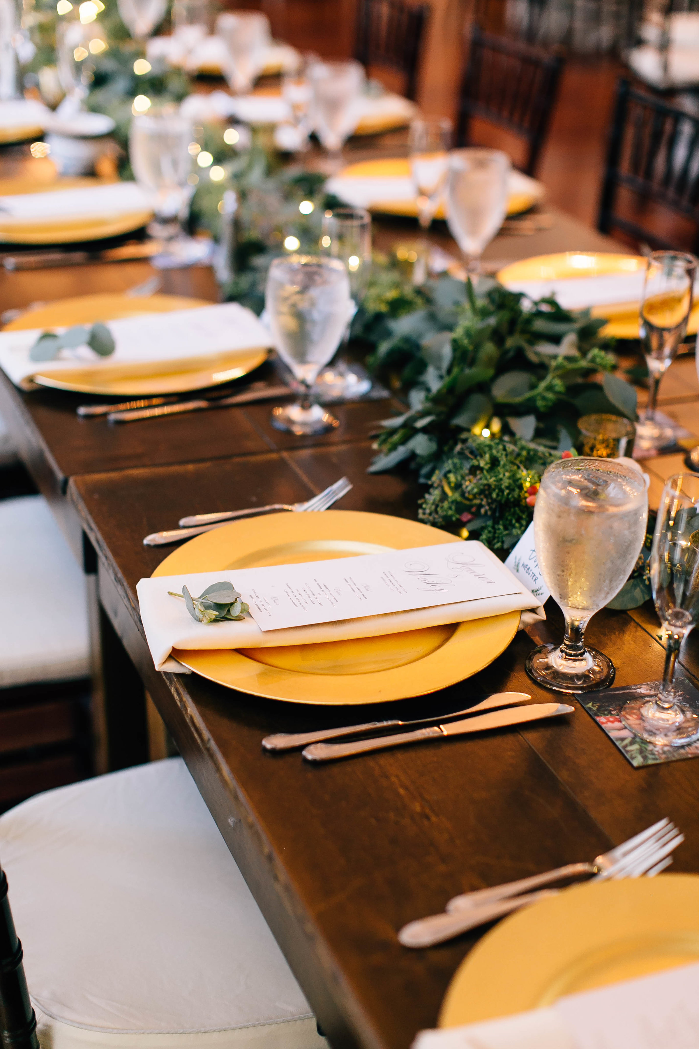 Orlando wedding planners tables with gold chargers, menus, & eucalyptus sprigs