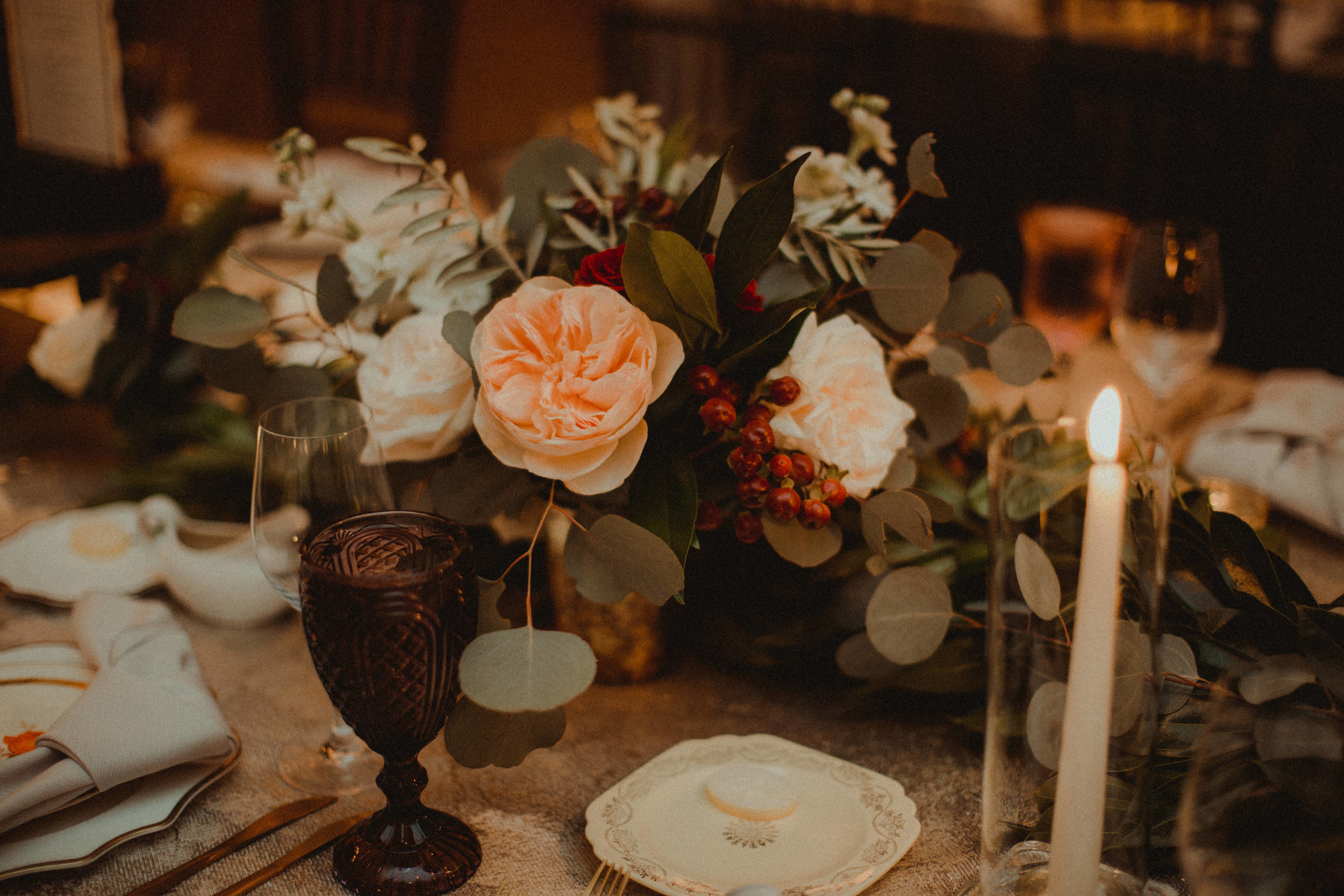 Floral centerpieces with red berries and blush juliet roses