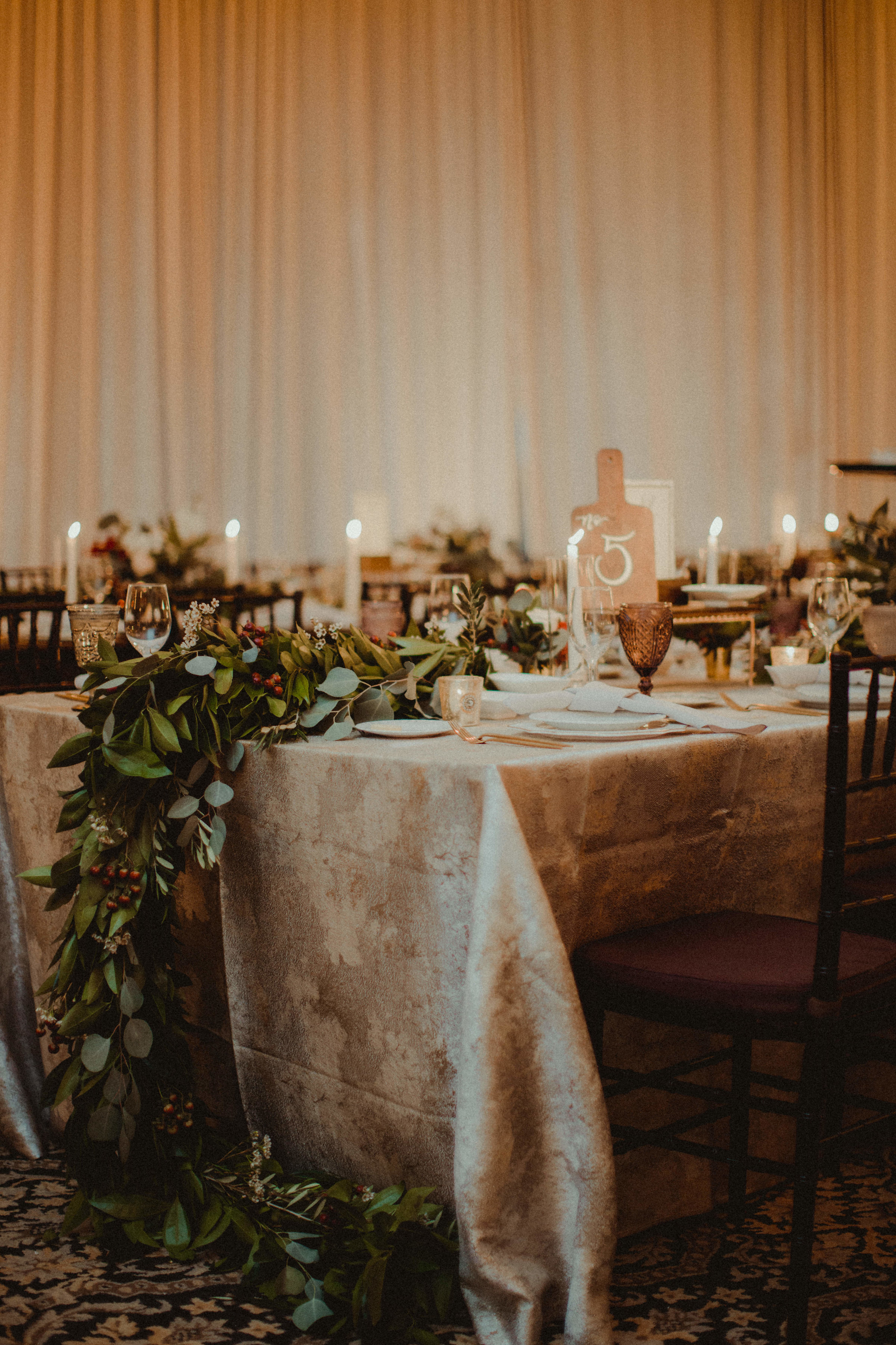 Family style banquet reception tables with garland table runners